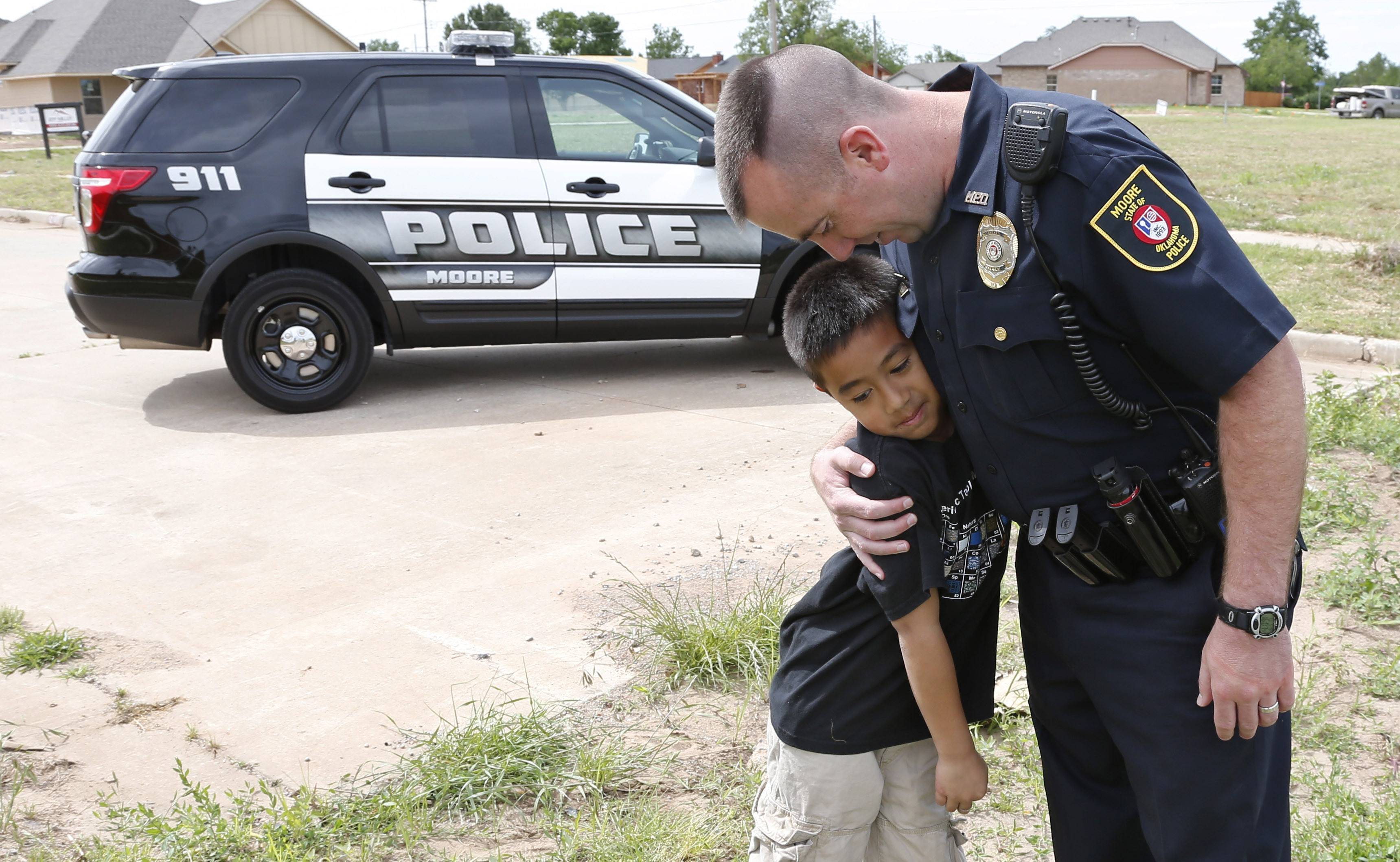 Moore police officer Travis Muehlenweg, right, hugs 10-year-old Kai Heuangpraseuth, after they met outside the new Plaza Towers Elementary school. Muehlenweg was photographed with Heuangpraseuth as he helped pull him from the rubble of Plaza Towers Elementary school following the 2013 tornado.