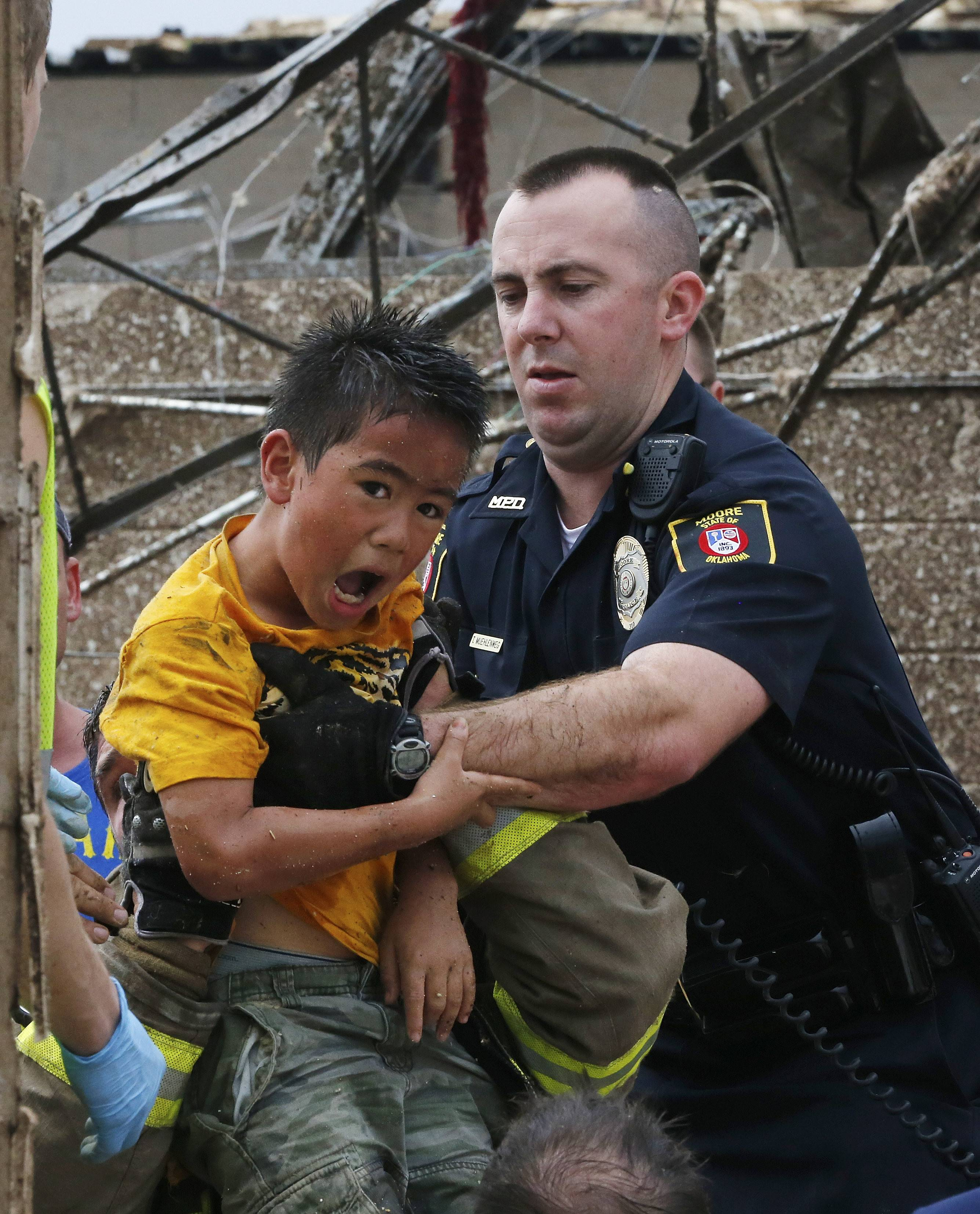 Kai Heuangpraseuth, age nine, is pulled from beneath a collapsed wall at the Plaza Towers Elementary School following a tornado in Moore, Okla.