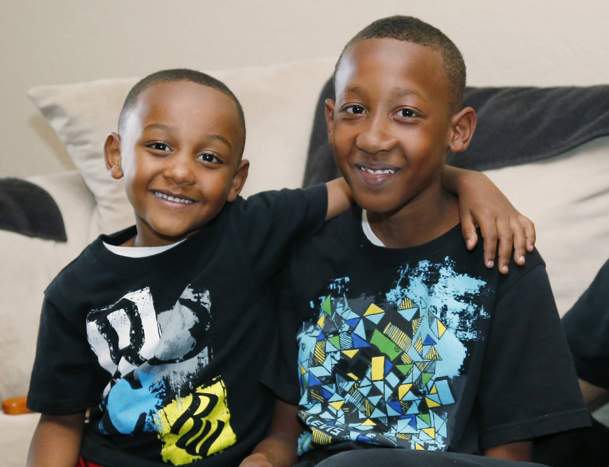 Anthony Richardson, left, 4, hugs his big brother, Cam'ron Richardson, right, at their home in Oklahoma City, Friday, May 16, 2014. Cam'ron was one of the third-grade students at Plaza Towers Elementary school who was trapped under a collapsed wall at the school following the May 20, 2013 tornado.