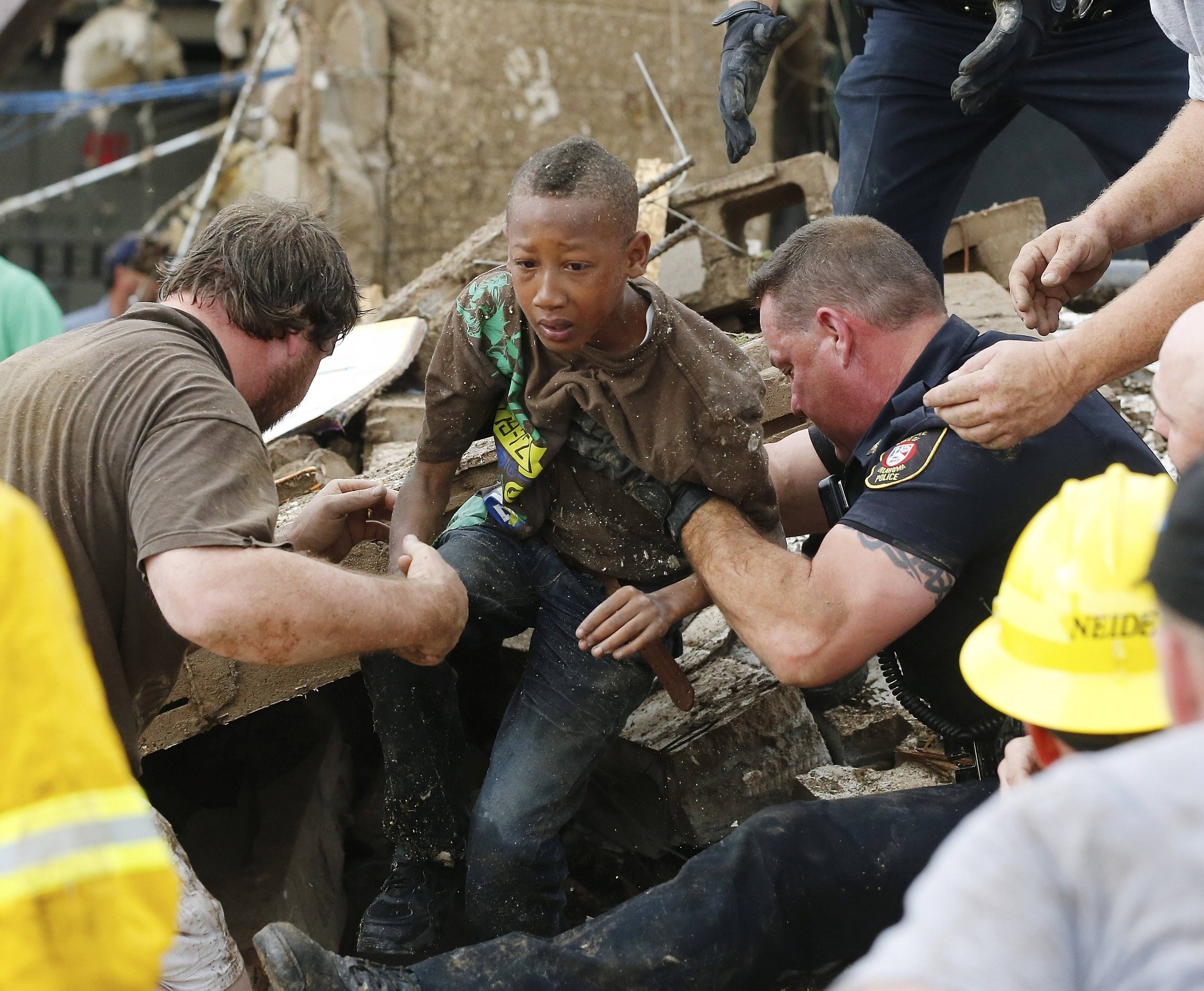 Cam'ron Richardson, center, is carried out of the rubble of Plaza Towers Elementary school in Moore, Okla.