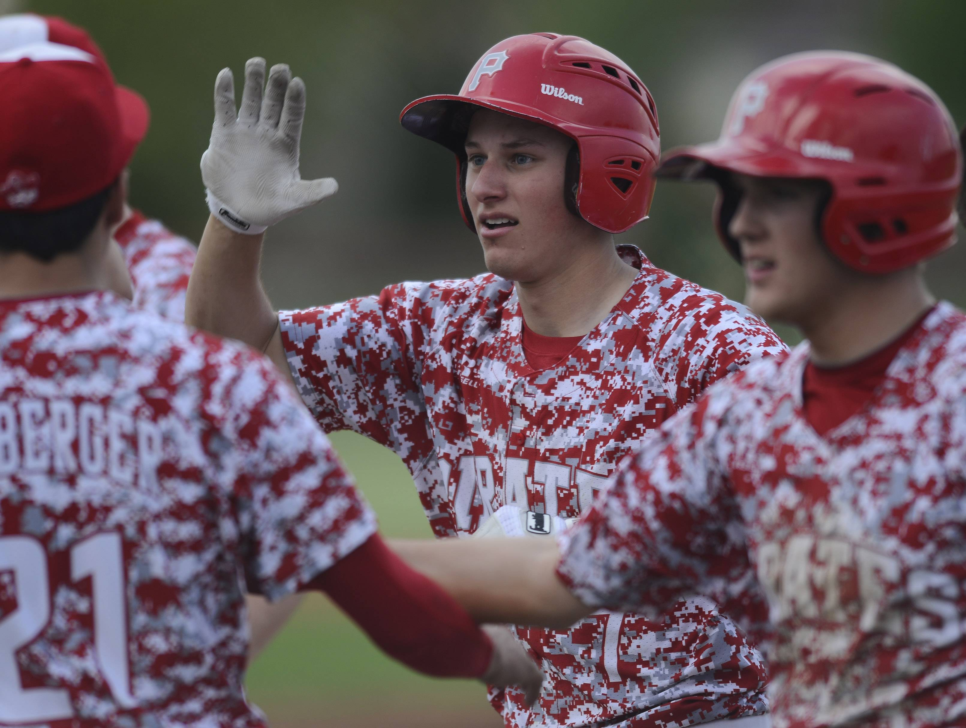 Palatine's Zach Serna celebrates his 2-run home run with teammates during the third inning of Tuesday's game at against Elk Grove.