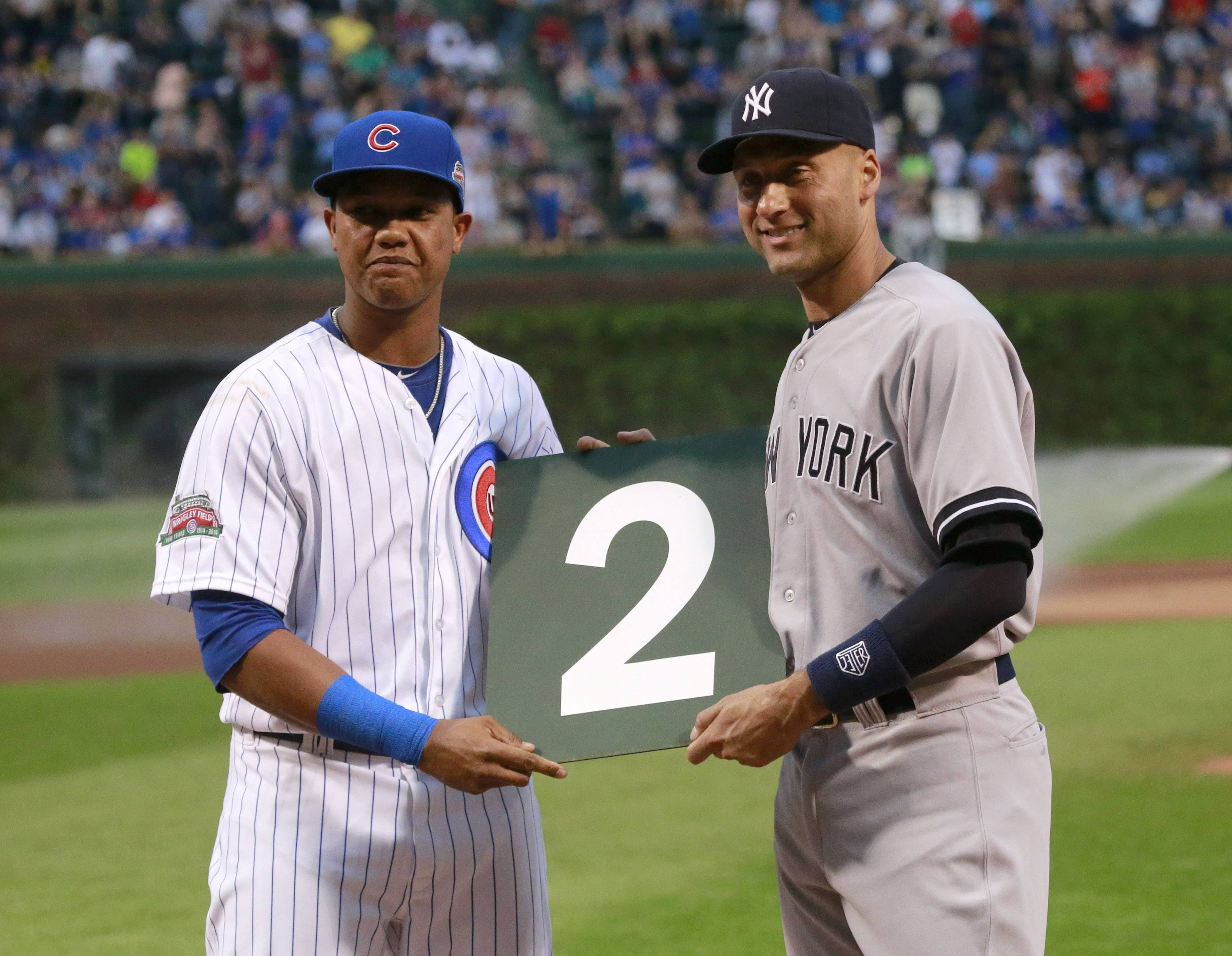 The Cubs' Starlin Castro, left, presents the Yankees' Derek Jeter with his uniform number from the Wrigley Field scoreboard Tuesday.