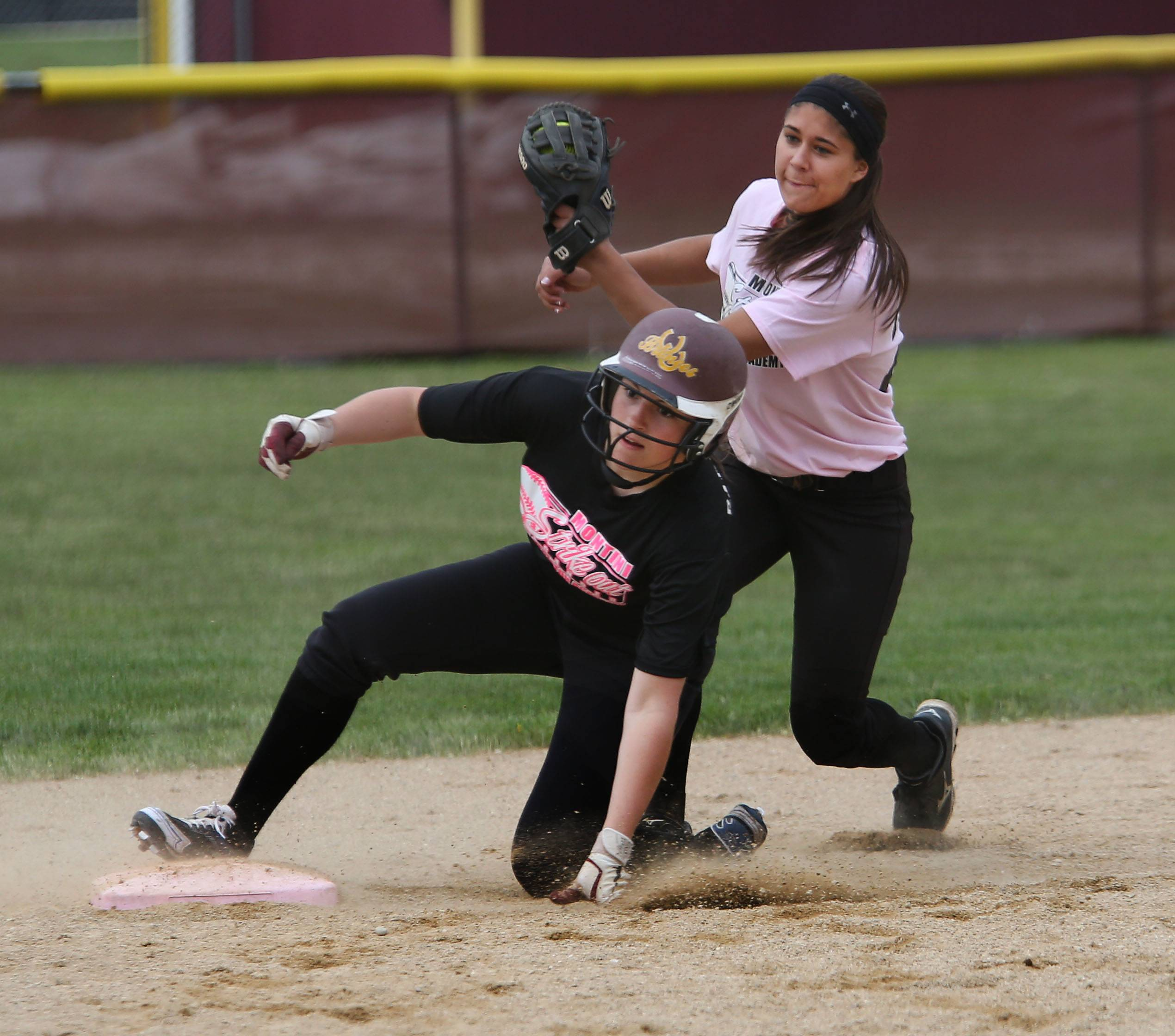 Montini's Ashley Lentine is safe at second base as Marissa Gagliano of Wheaton Academy, right, tries to tag her out during softball action in Lombard on Monday.