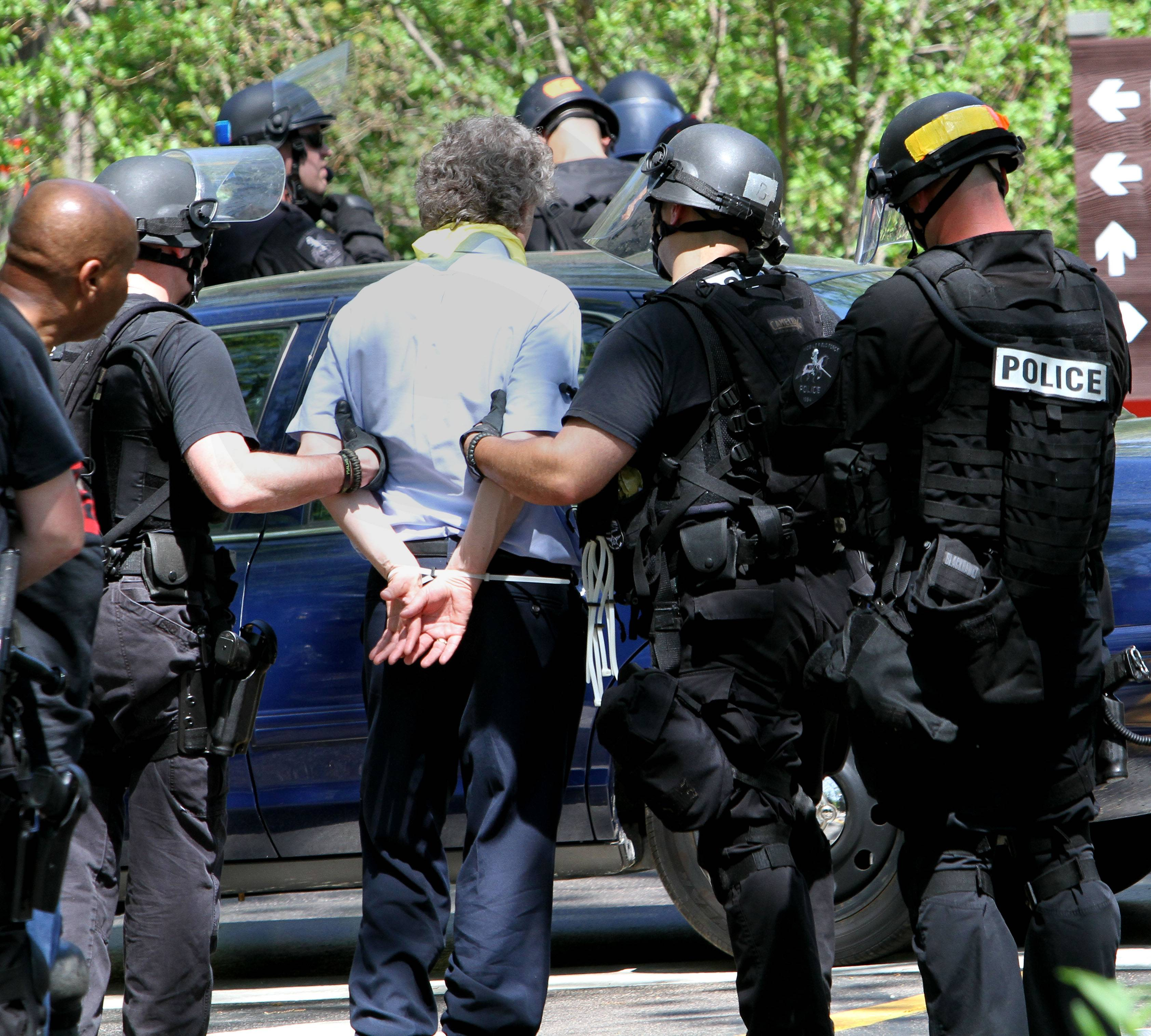 Police arrest a protester at McDonald's campus in Oak Brook on Wednesday.