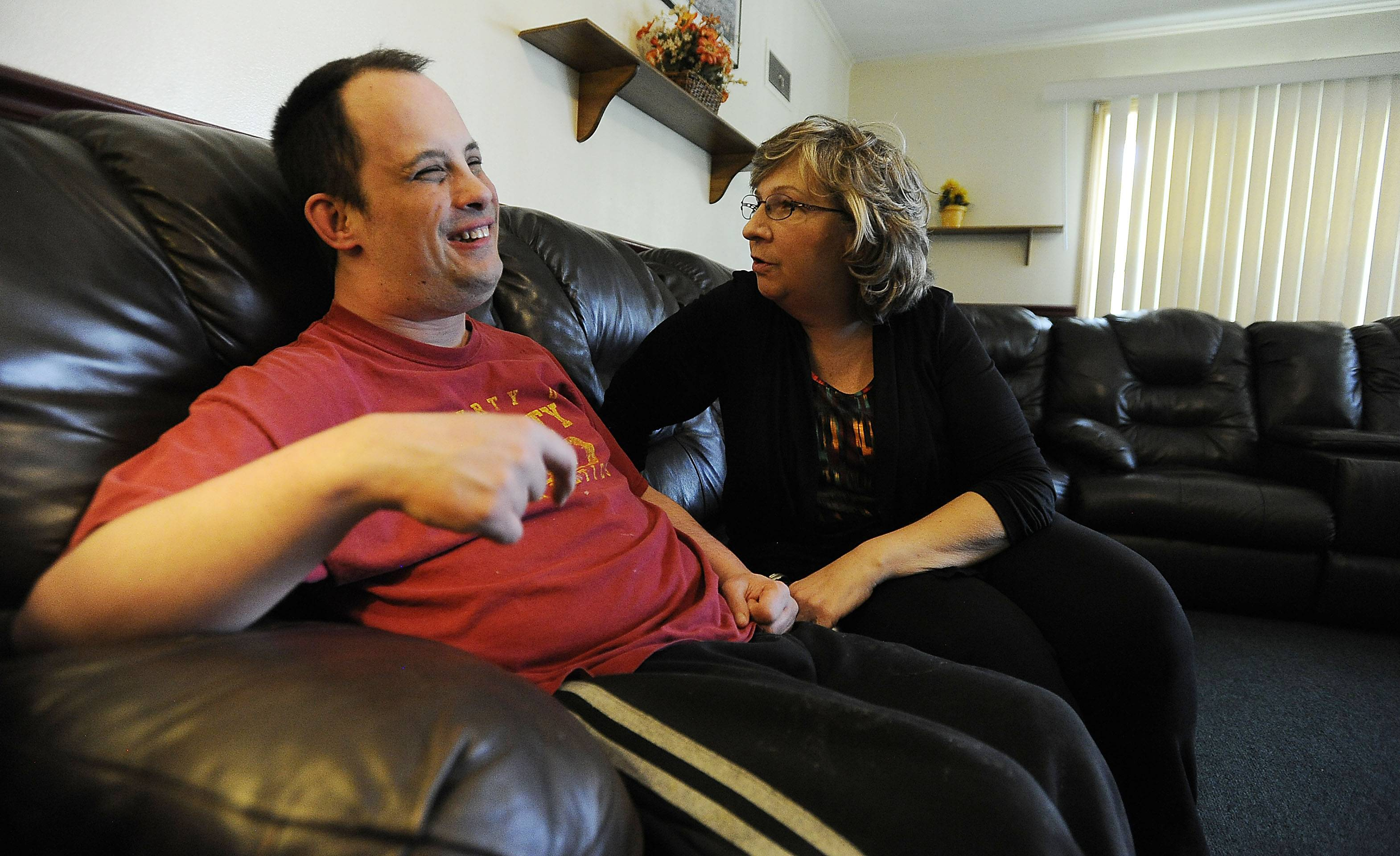 Caregiver Neoma Spencer of Hoffman Estates shares a moment with Michael Voekner at his home in Des Plaines for the disabled after he came home from work.