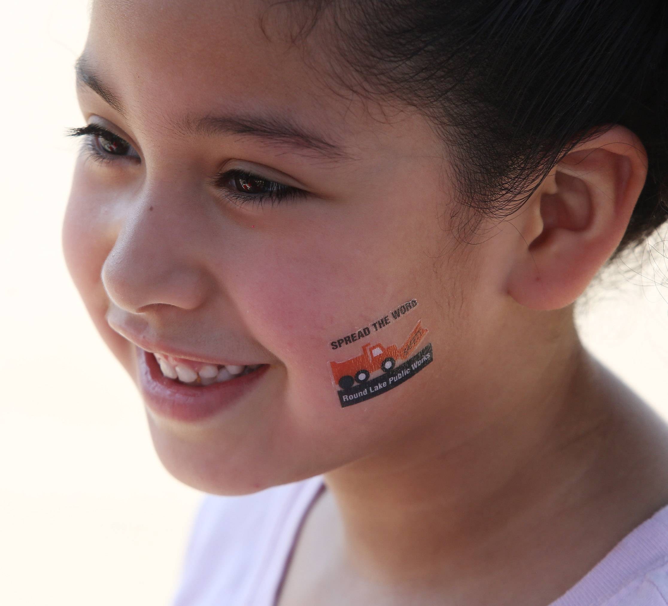 Sara Robledo, 6, of Fox Lake, displays a Round Lake Public Works tattoo during the first Round Lake Public Works Open House. Wednesday's event featured public works, police and fire vehicles.