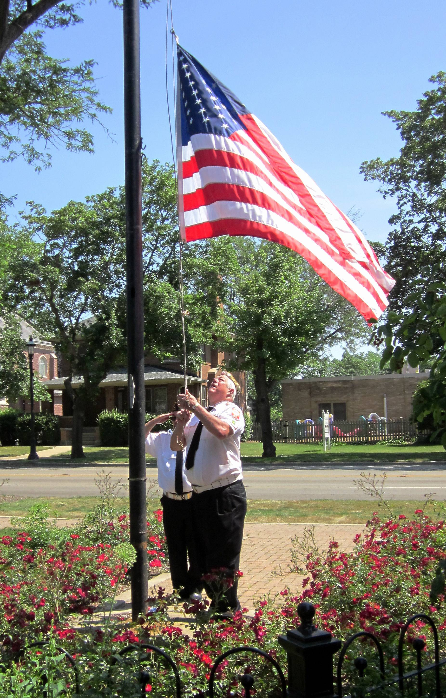 Larry Fettes, of VFW Post 2298, brings the flag down to half staff for a Memorial Day ceremony in Grafelman Park in West Dundee. George Cochran salutes the flag behind him. Post 2298 organizes the annual Memorial Day parade and program, which starts in East Dundee and ends in West Dundee.