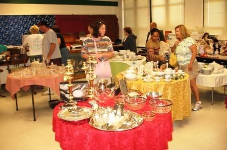 Shoppers at a previous Prince of Peace rummage sale browse the kitchenware.