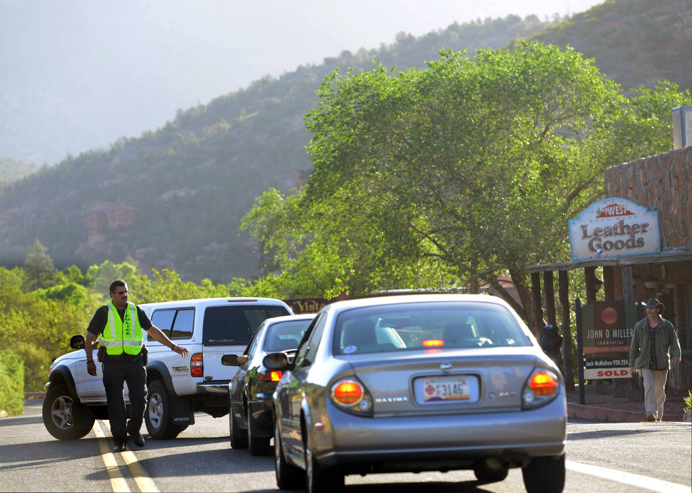 Sedona Police close off Oak Creak Canyon and turn around traffic in downtown Sedona, Ariz. near the downtown Sedona Arts Center on Wednesday, May 21, 2014, as fire crews work on a wildfire that closed 89A in the canyon, a popular tourist road.