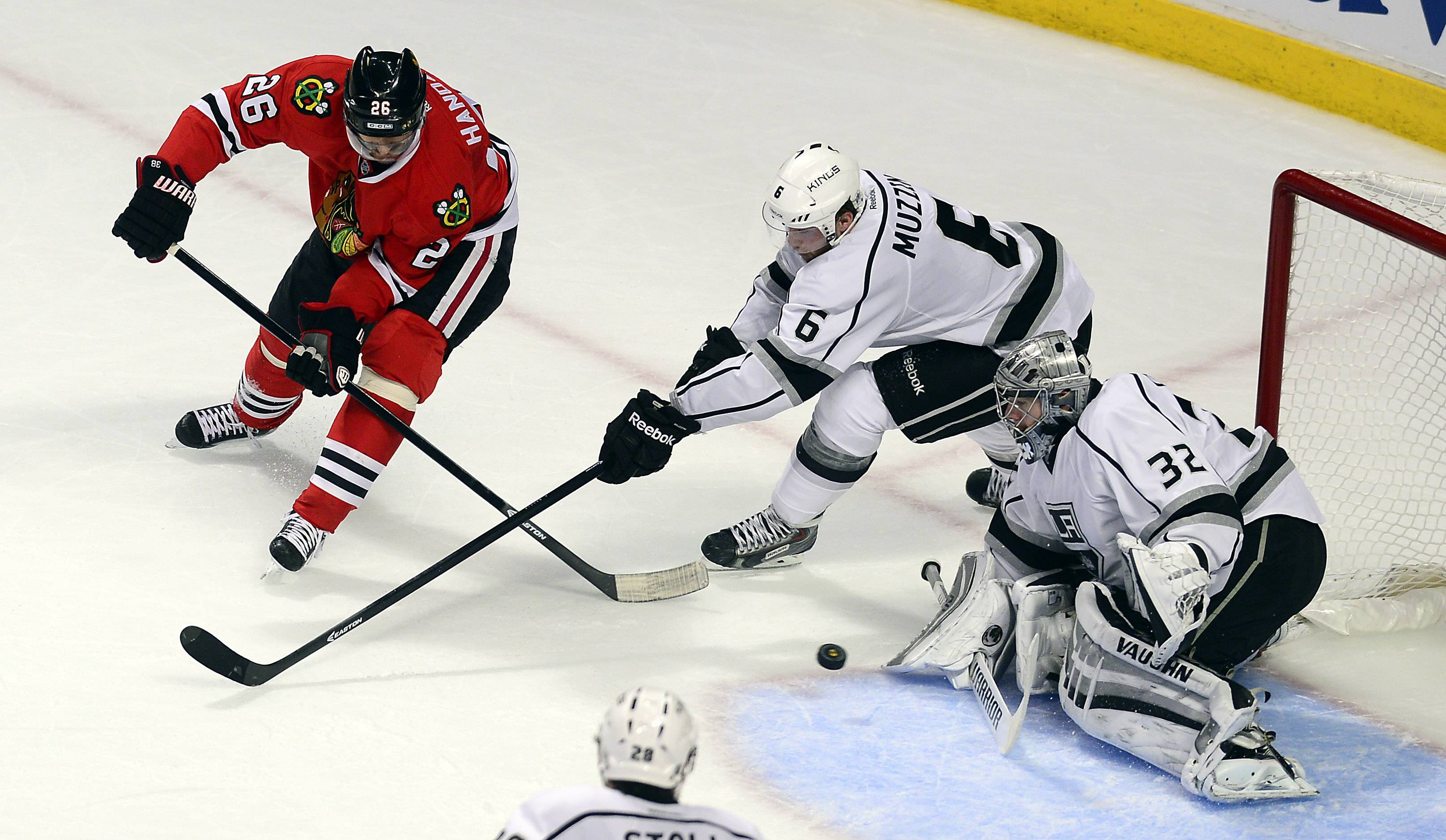 Blackhawks Michal Handzus shoots in the second period against Los Angeles goalie Jonathan Quick and Jake Muzzin in Game 2.