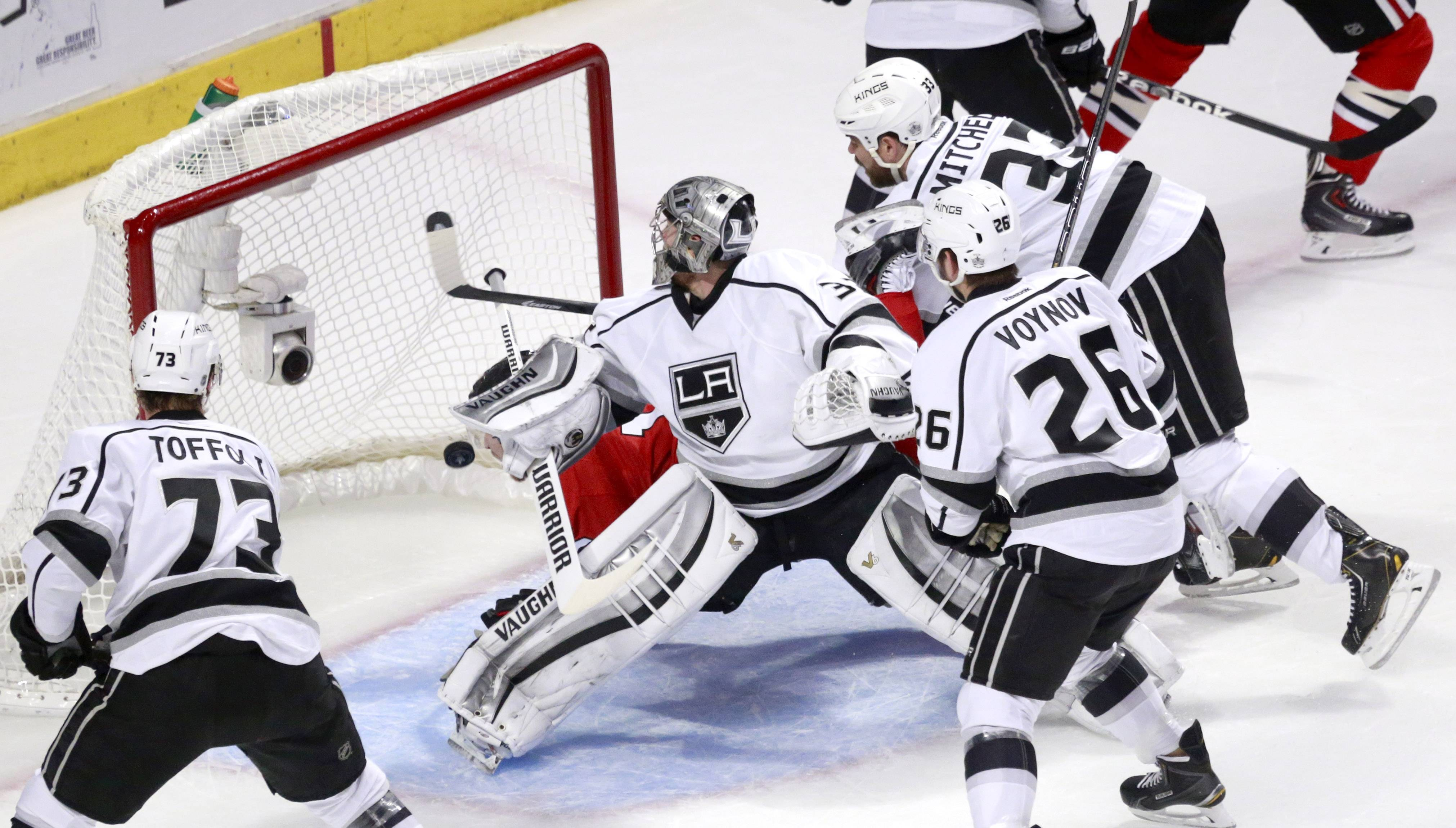 Chicago Blackhawks center Peter Regin, is crosschecked into the goal by Los Angeles Kings defenseman Willie Mitchell (33) past Los Jonathan Quick (32) as Tyler Toffoli (73) and Slava Voynov watch during the first period of Game 2 of the Western Conference finals in the NHL hockey Stanley Cup playoffs Wednesday, May 21, 2014, in Chicago. The play was reviewed and no goal was allowed.