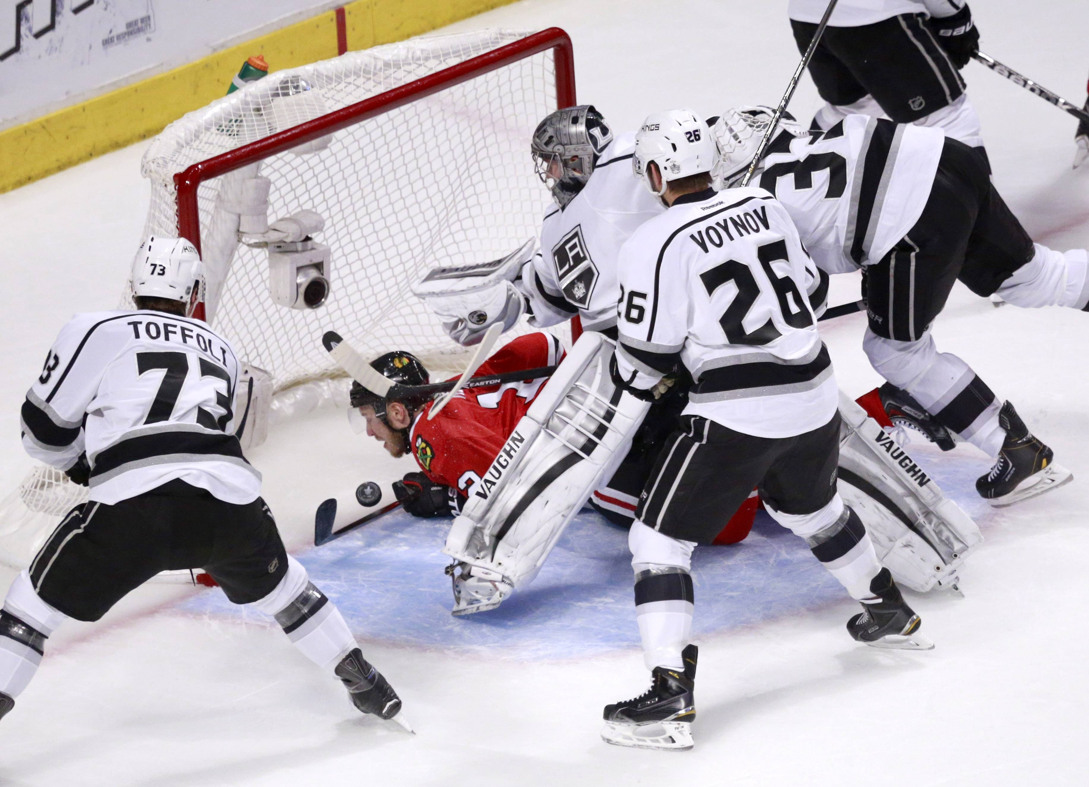 Blackhawks center Peter Regin gets crosschecked into the goal by Kings defenseman Willie Mitchell past goalie Jonathan Quick as Tyler Toffoli and Slava Voynov watch during the first period Wednesday. The Hawks went on a power play and cashed in when Nick Leddy beat Jonathan Quick with a backhander.
