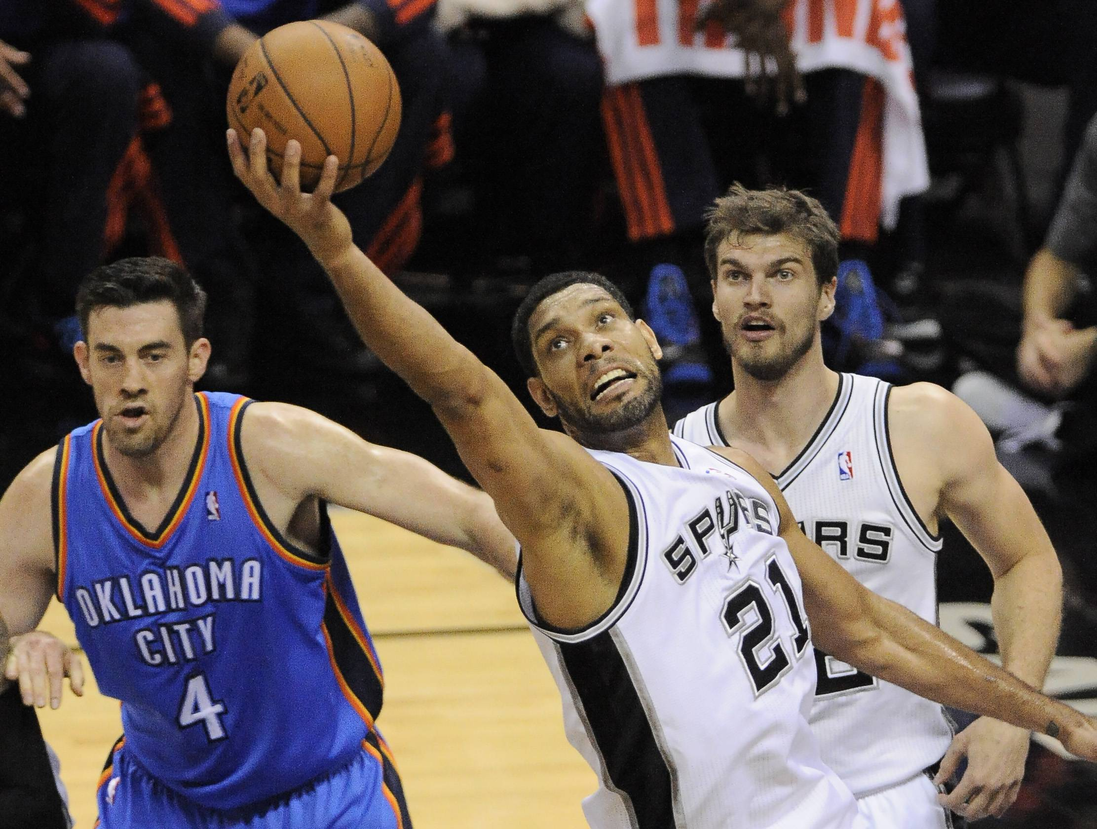 San Antonio Spurs forward Tim Duncan (21) grabs a rebound as Oklahoma City Thunder forward Nick Collison (4) and Spurs forward Tiago Splitter, of Brazil, watch during the first half of Game 2 of the Western Conference finals NBA basketball playoff series, Wednesday, May 21, 2014, in San Antonio.