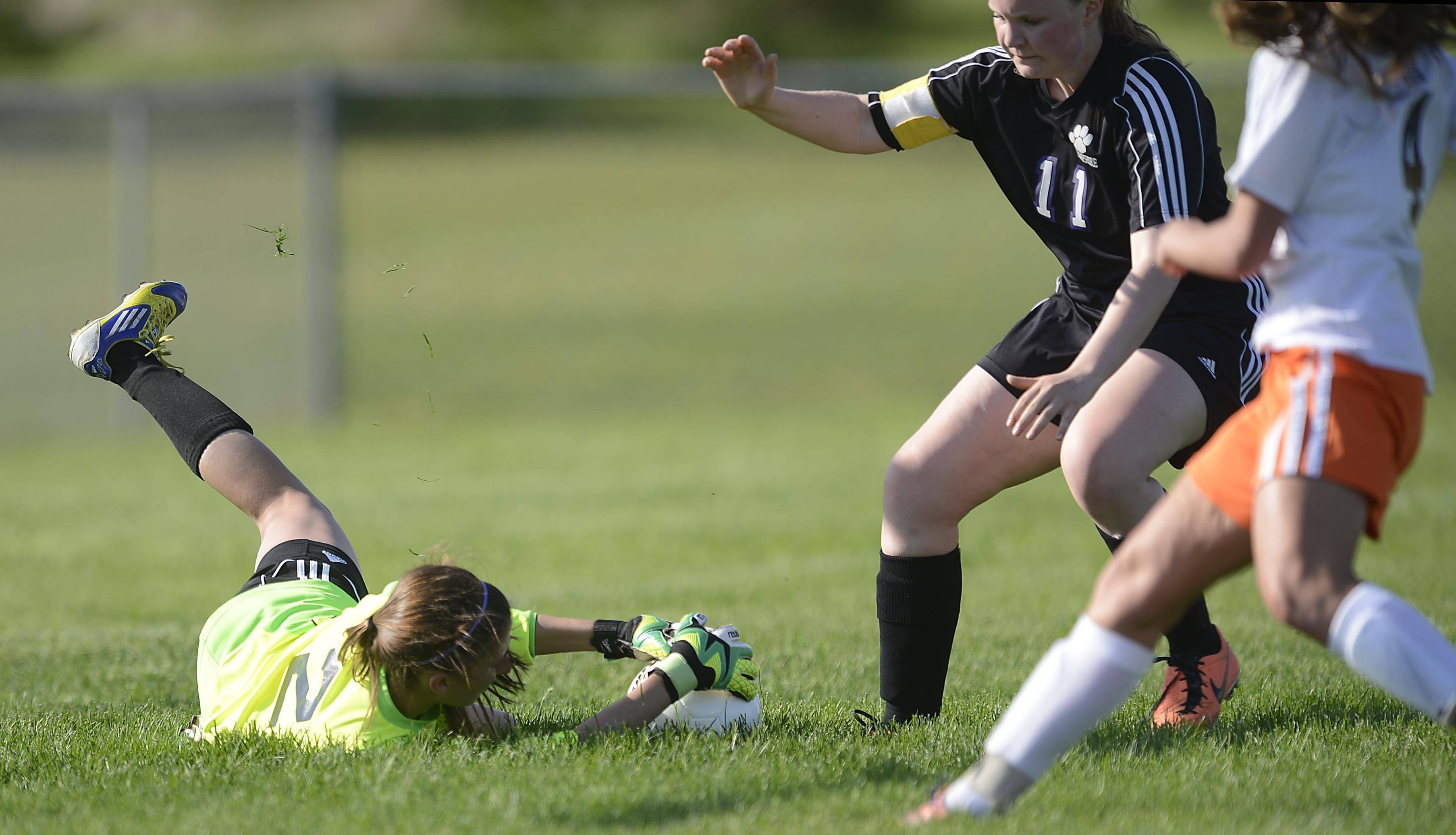 John Starks/jstarks@dailyherald.comHampshire goalkeeper Kaila Kienzler makes a stop as teammate McCall Rafferty blocks DeKalb's Morgan Beaty Wednesday in the Class 2A Burlington Central regional game.