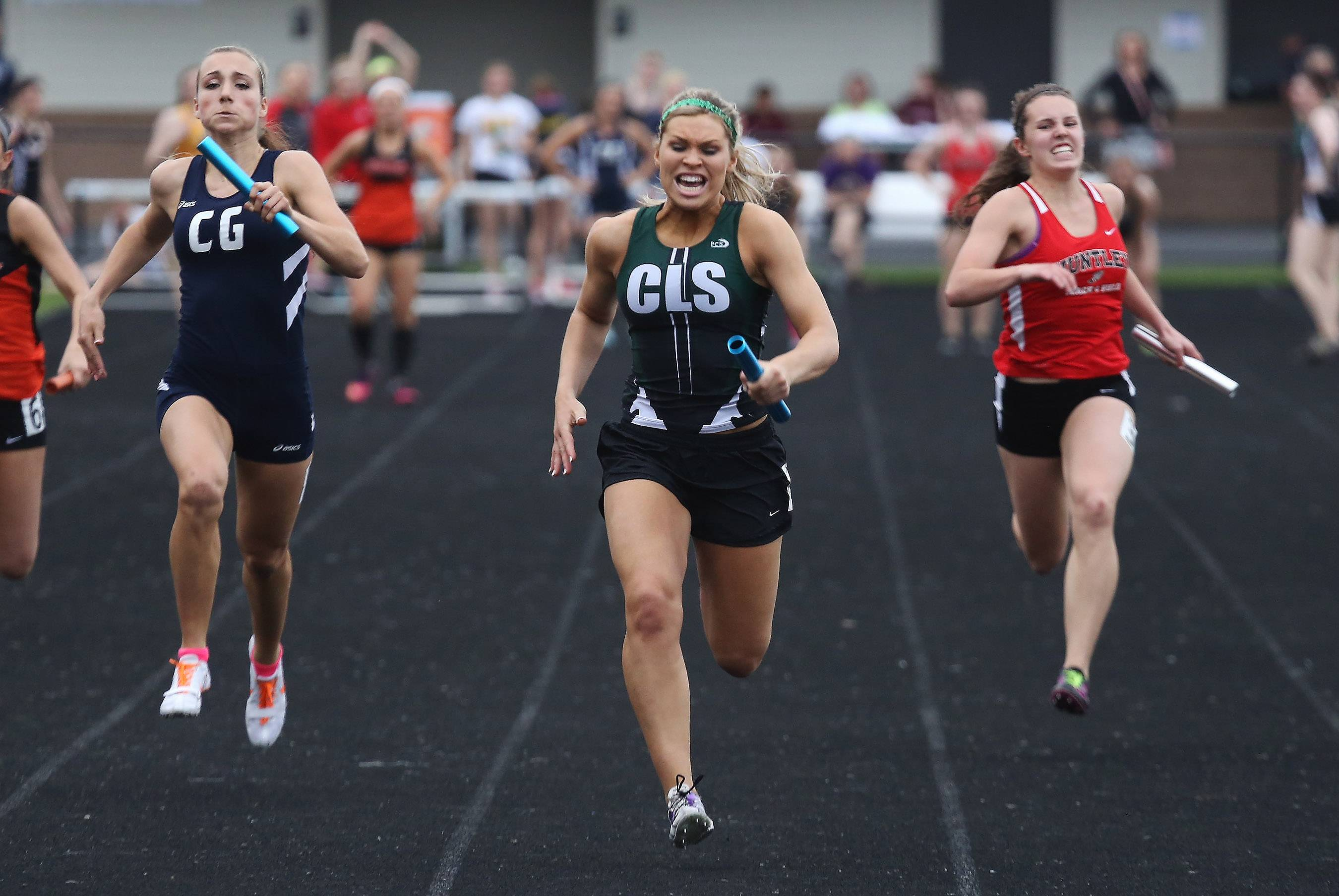 Taylor Schau of the Crystal Lake South team wins the 4x100 meter really during the Fox Valley Conference girls track meet. Eva Burke of Cary-Grove is left and Tina Driscoll of Huntley is right.