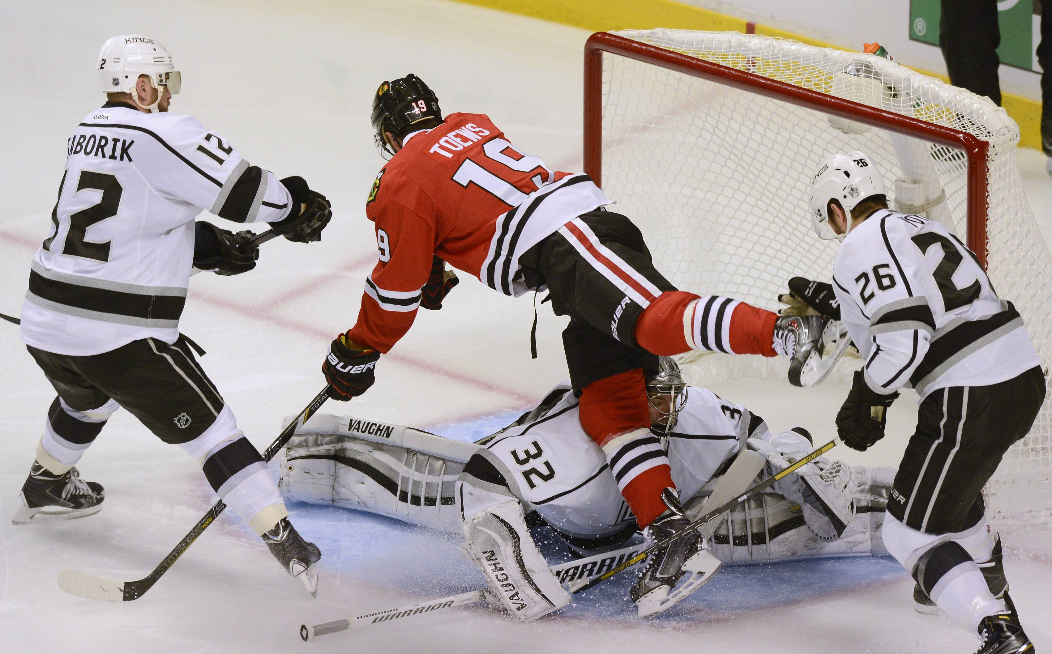 Blackhawks center Jonathan Toews makes contact with Los Angeles Kings goalie Jonathan Quick on a goal that wound up being disallowed during Sunday's game at United Center. Los Angeles Kings forward Marian Gaborik is at left, and teammate Slava Voynov is at right.