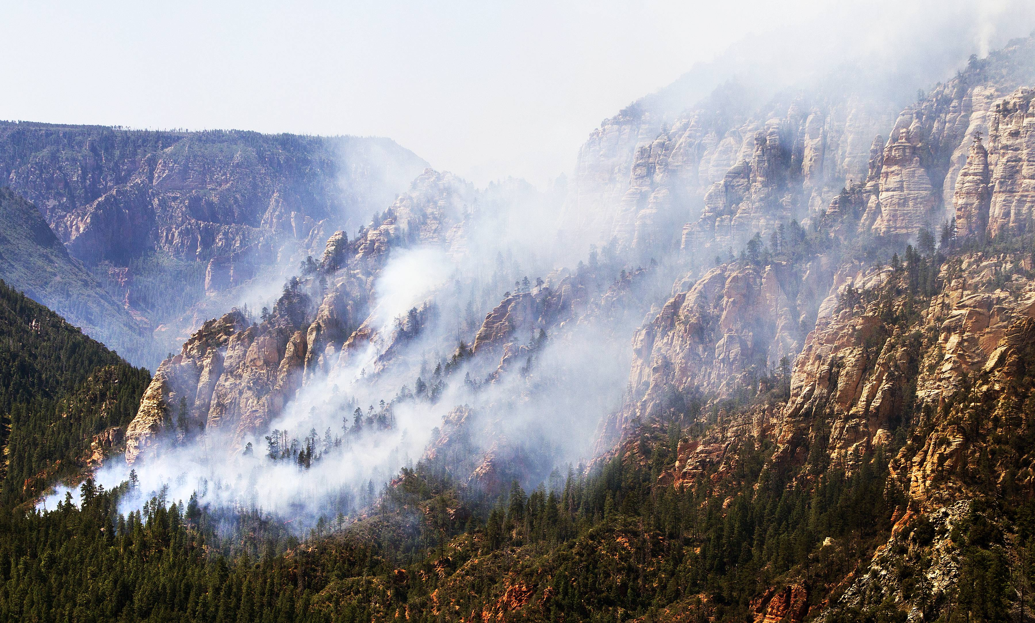 A wildfire that started in a scenic canyon snaked toward Flagstaff on Thursday, prompting residents of outlying areas to prepare to flee and blanketing the city in smoke.