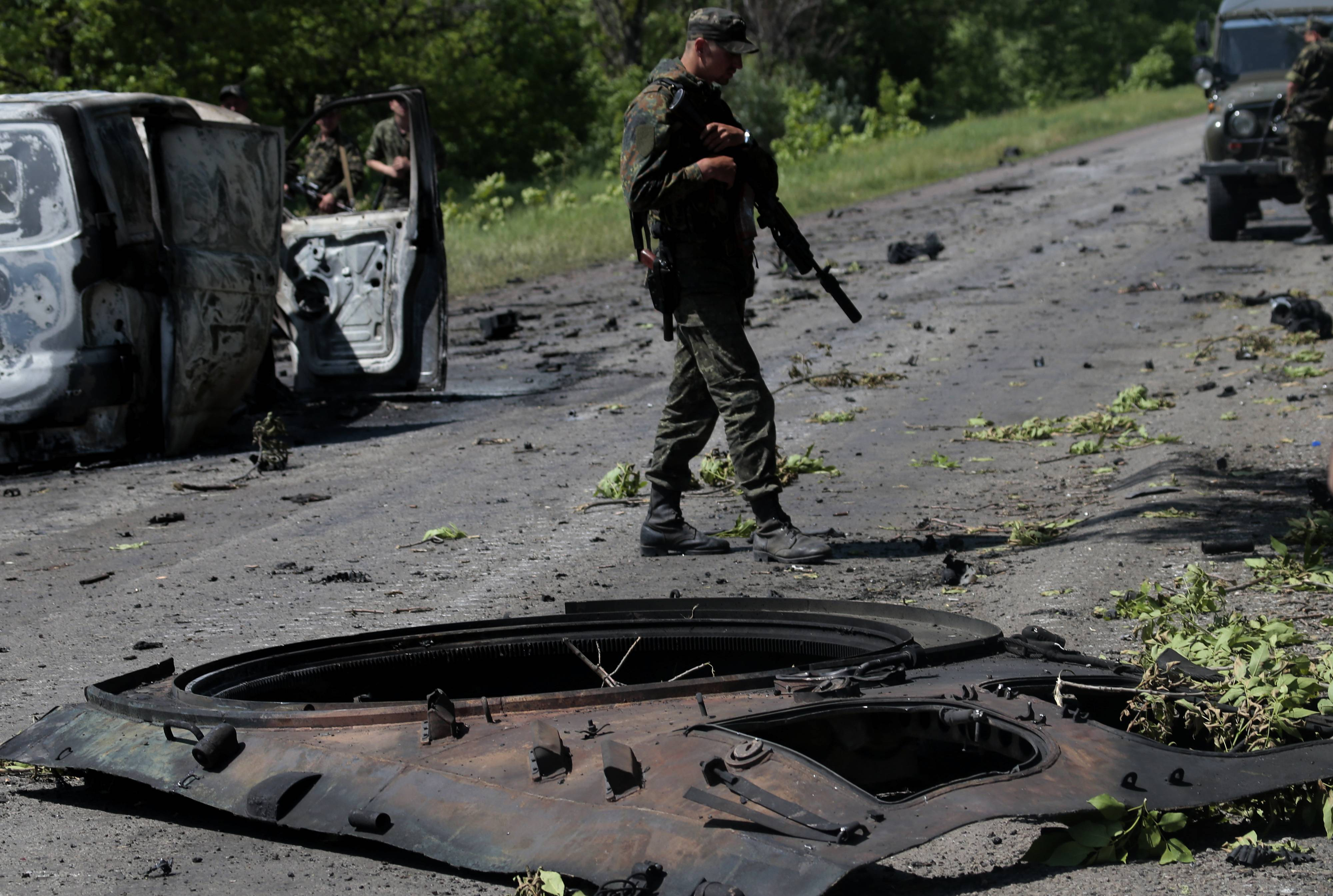 A Ukrainian soldier surveys the site of a battle near the village of Blahodatne, eastern Ukraine, Thursday, where 16 Ukrainian troops were killed and about 30 others were wounded when Pro-Russians attacked a military checkpoint.
