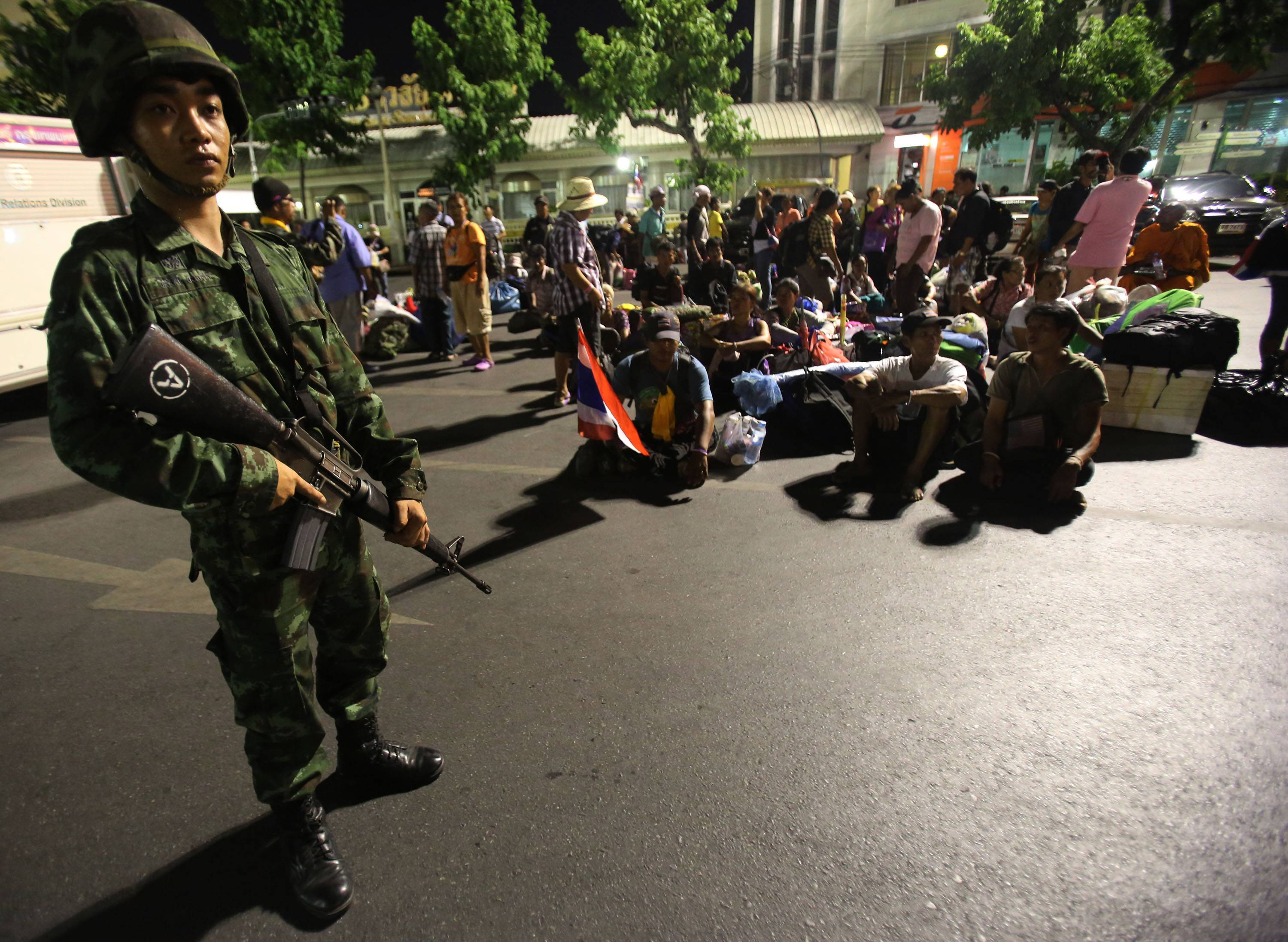 A Thai soldier stands guard over anti-government demonstrators with their belongings, as they leave their demonstration site after soldiers staged a coup Thursday in Bangkok.