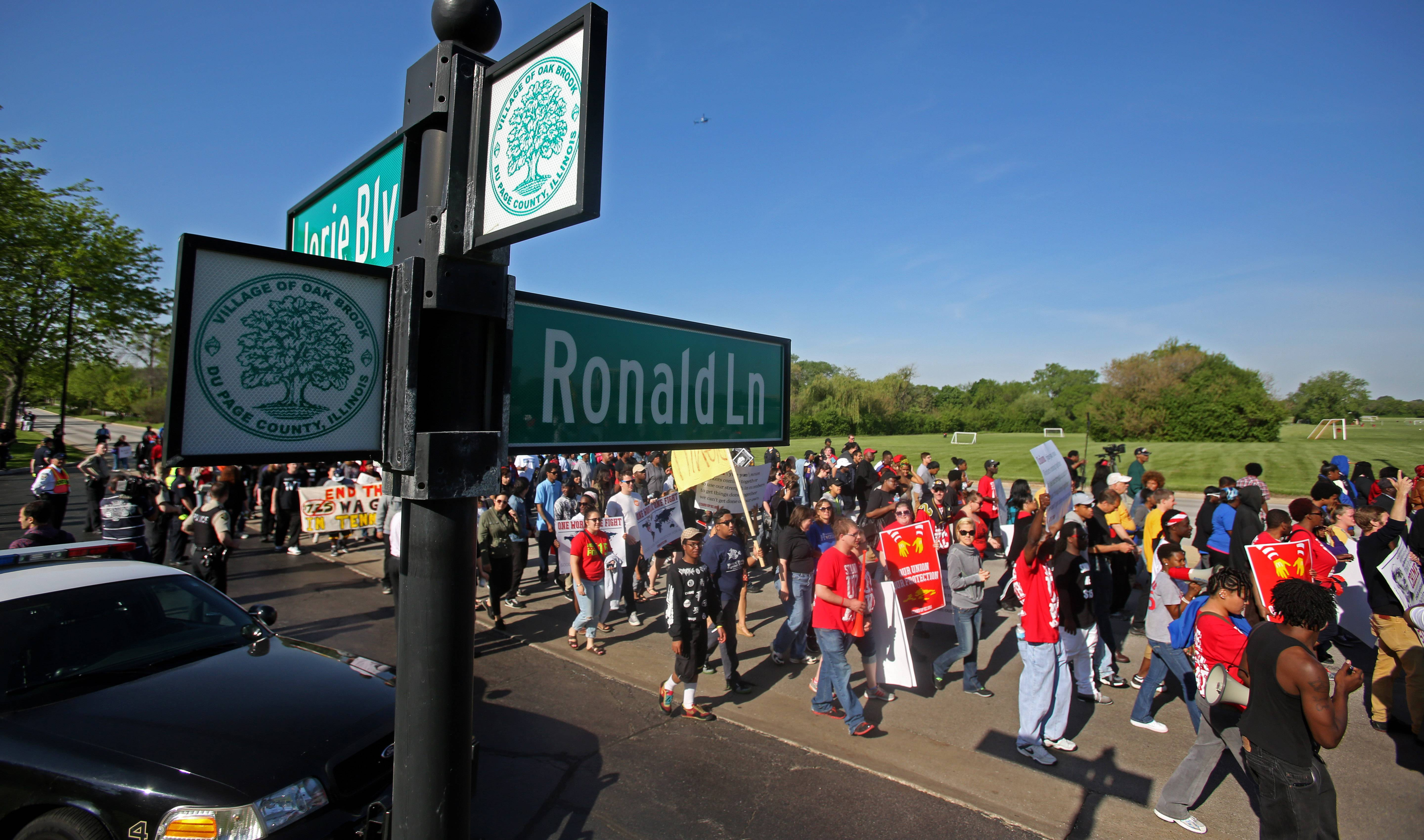 Protesters march along Jorie Boulevard during a demonstration for higher fast food wages outside McDonald's headquarters.