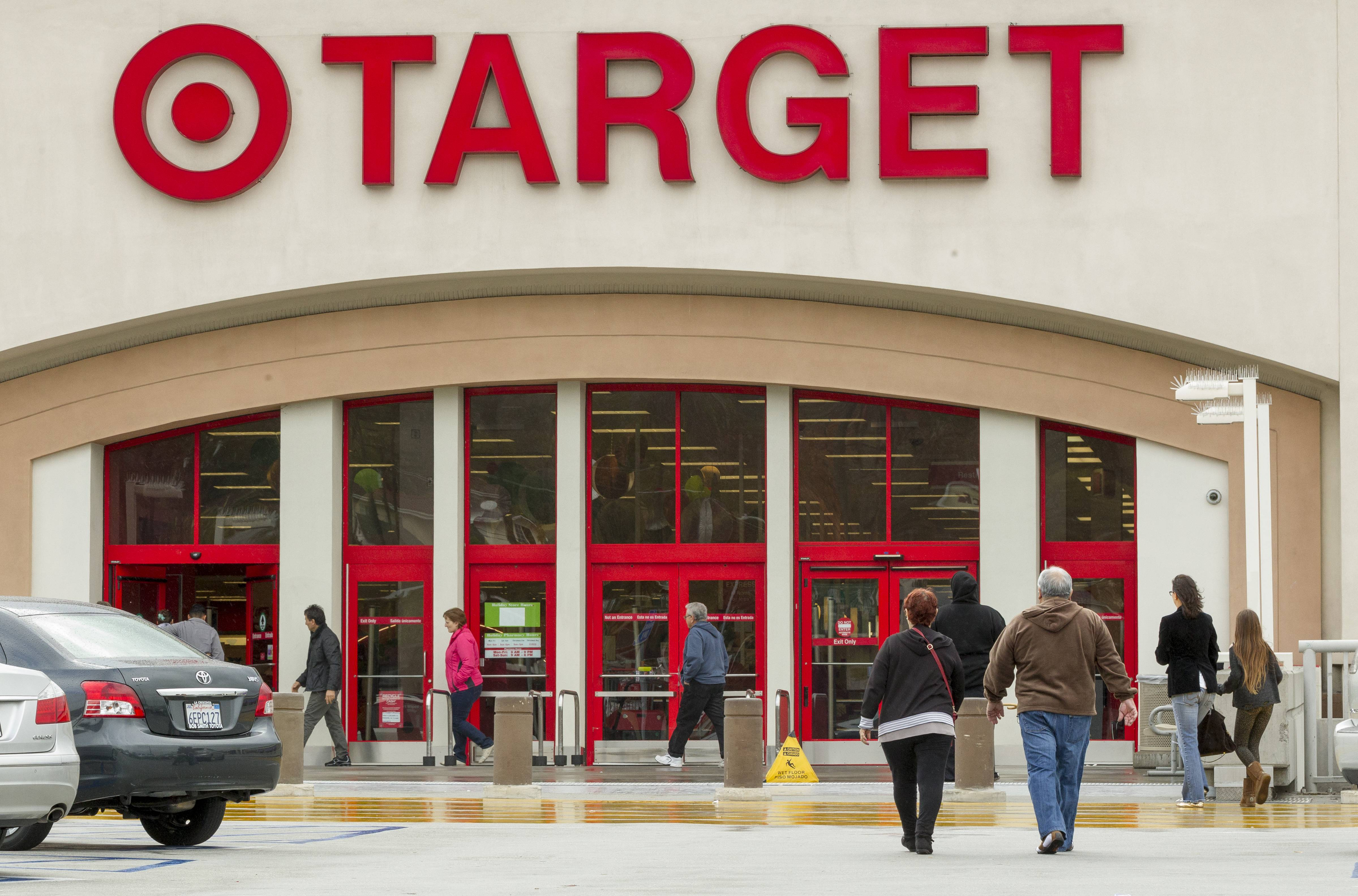 Target cut its annual profit outlook Wednesday and said its first-quarter earnings fell 16 percent as it took another hit from a massive customer data breach and a troubled expansion in Canada.
