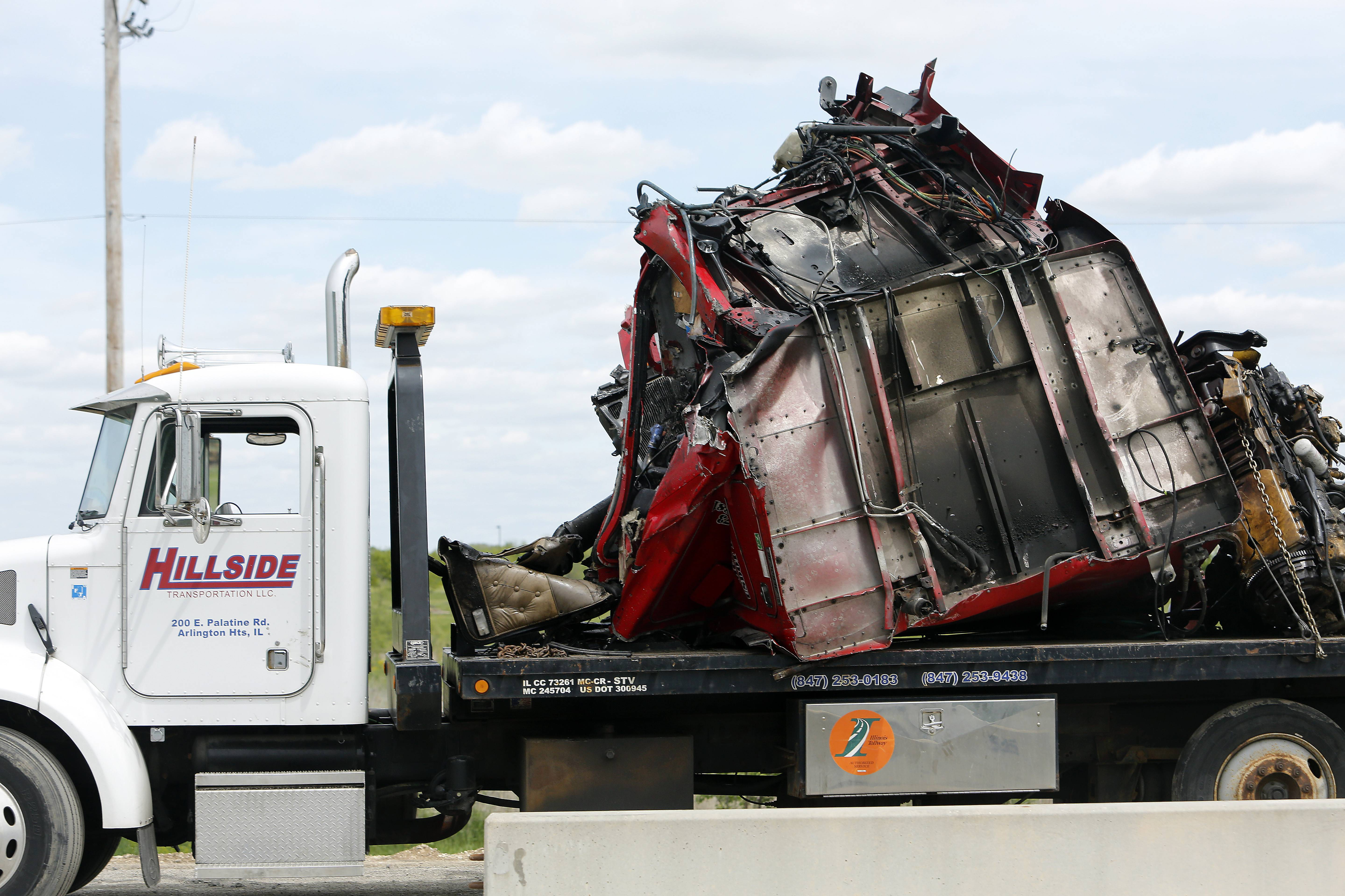 The remains of a truck sit on a flatbed on the shoulder of westbound Interstate 90 Thursday after a crash involving three semitrailers. Illinois State Police was investigating the crash near Huntley in which one truck driver was injured.