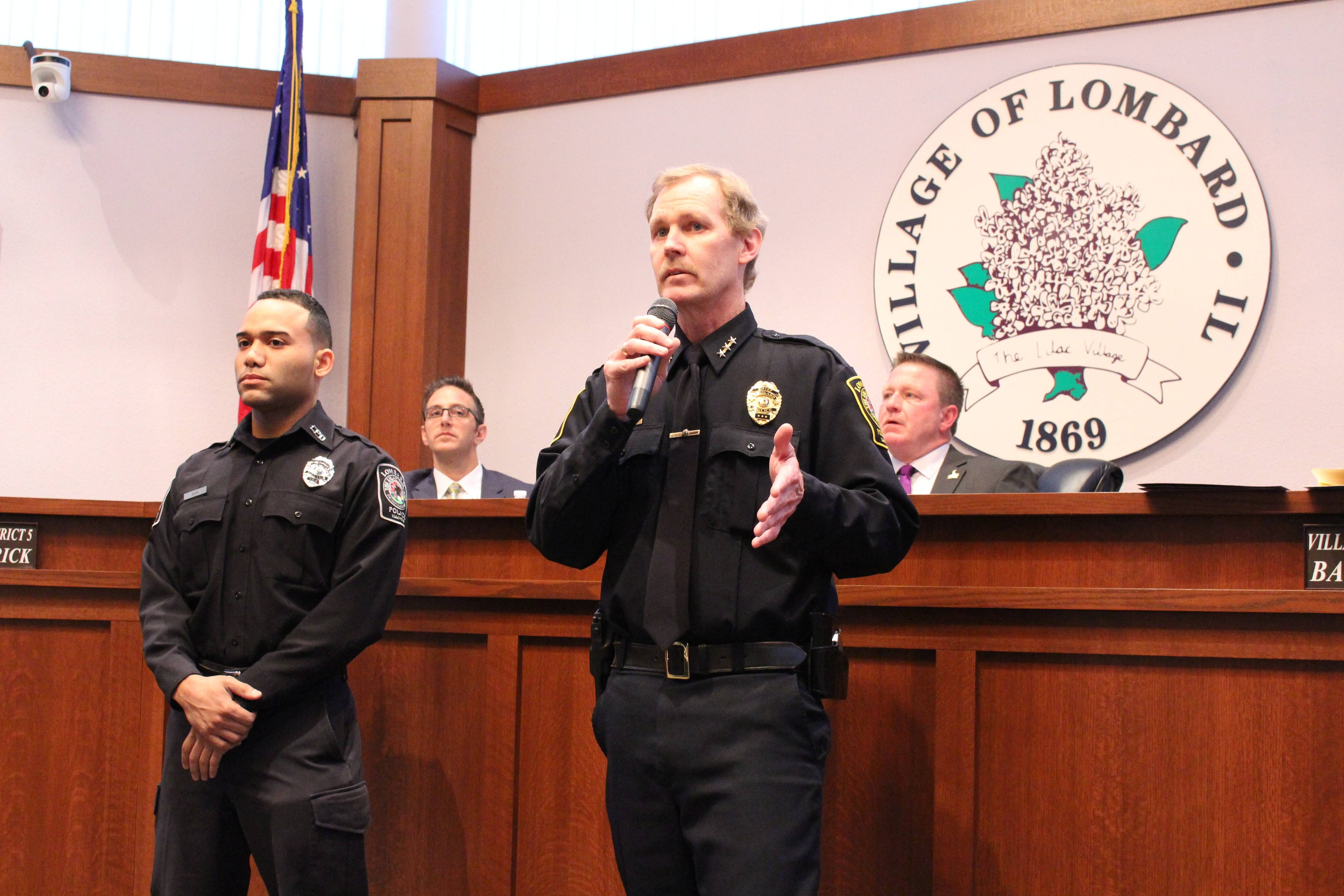 Lombard police Chief Raymond Byrne, right, presents the Award of Valor to officer Scott Jean.