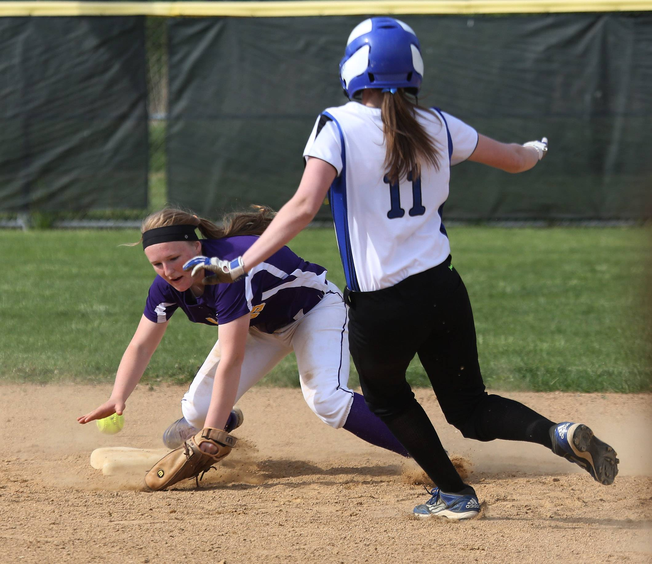 Lake Zurich's Rachel Dawson slides into second after Wauconda shortstop Lauren Nee tries to handle the ball during the second inning of Thursday's NSC championship game at Wauconda.