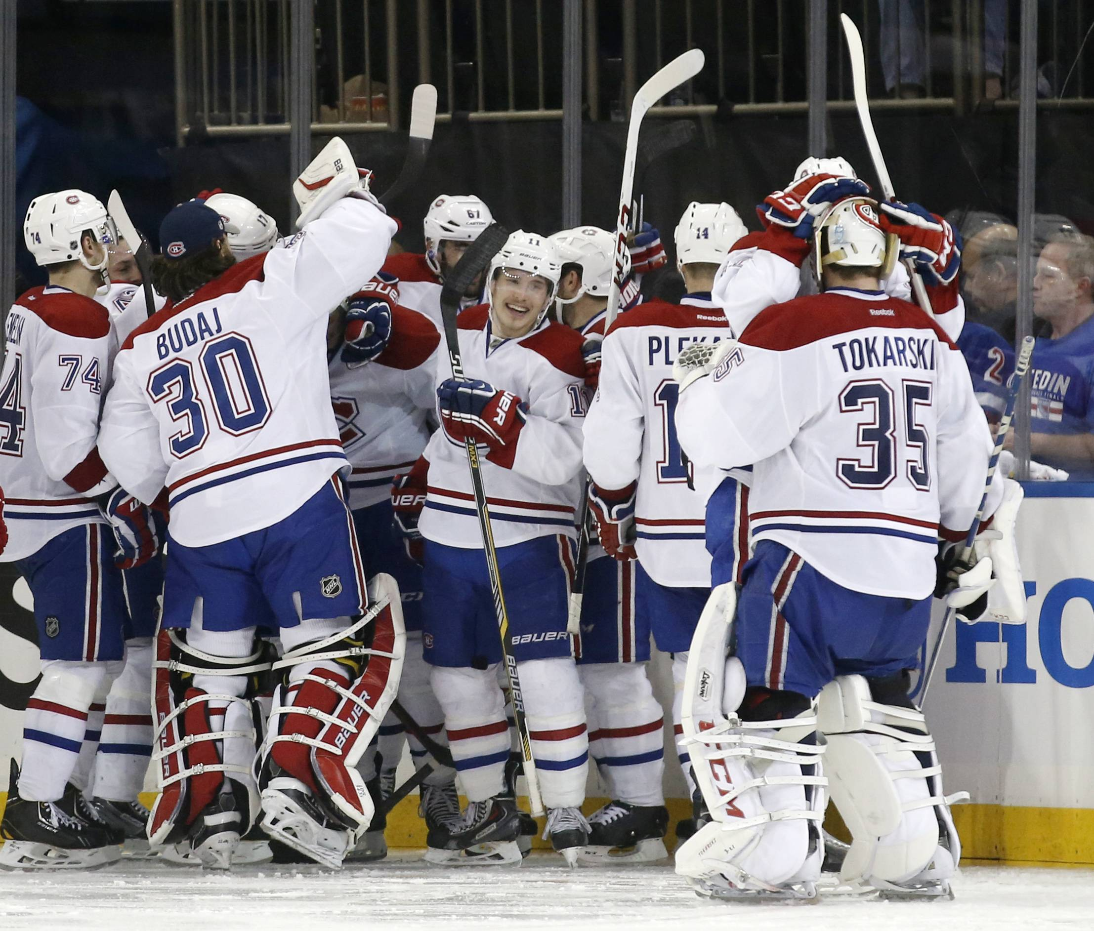 The Montreal Canadiens celebrate after defeating the New York Rangers 3-2 in overtime in Game 3 of the NHL hockey Stanley Cup playoffs Eastern Conference finals, Thursday, May 22, 2014, in New York.