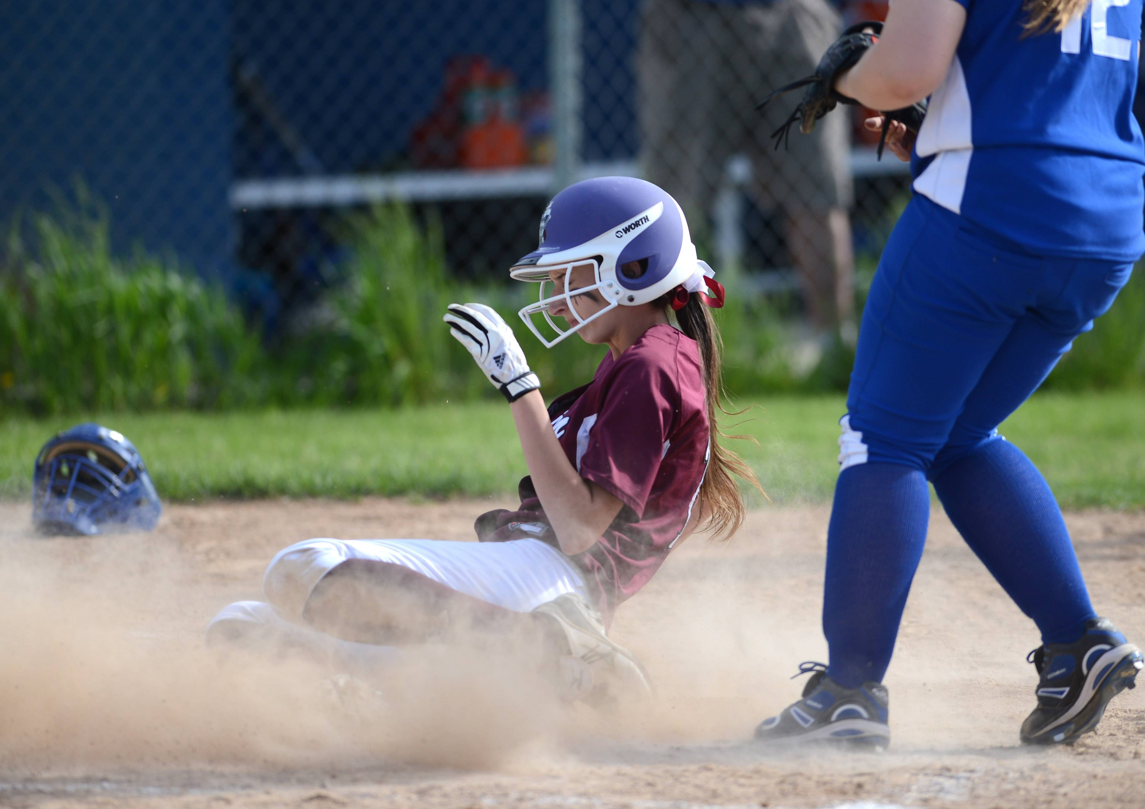 Elgin's Jenna Lombardo (1) slides safely into home on a wild pitch during Thursday's game at Larkin in Elgin.