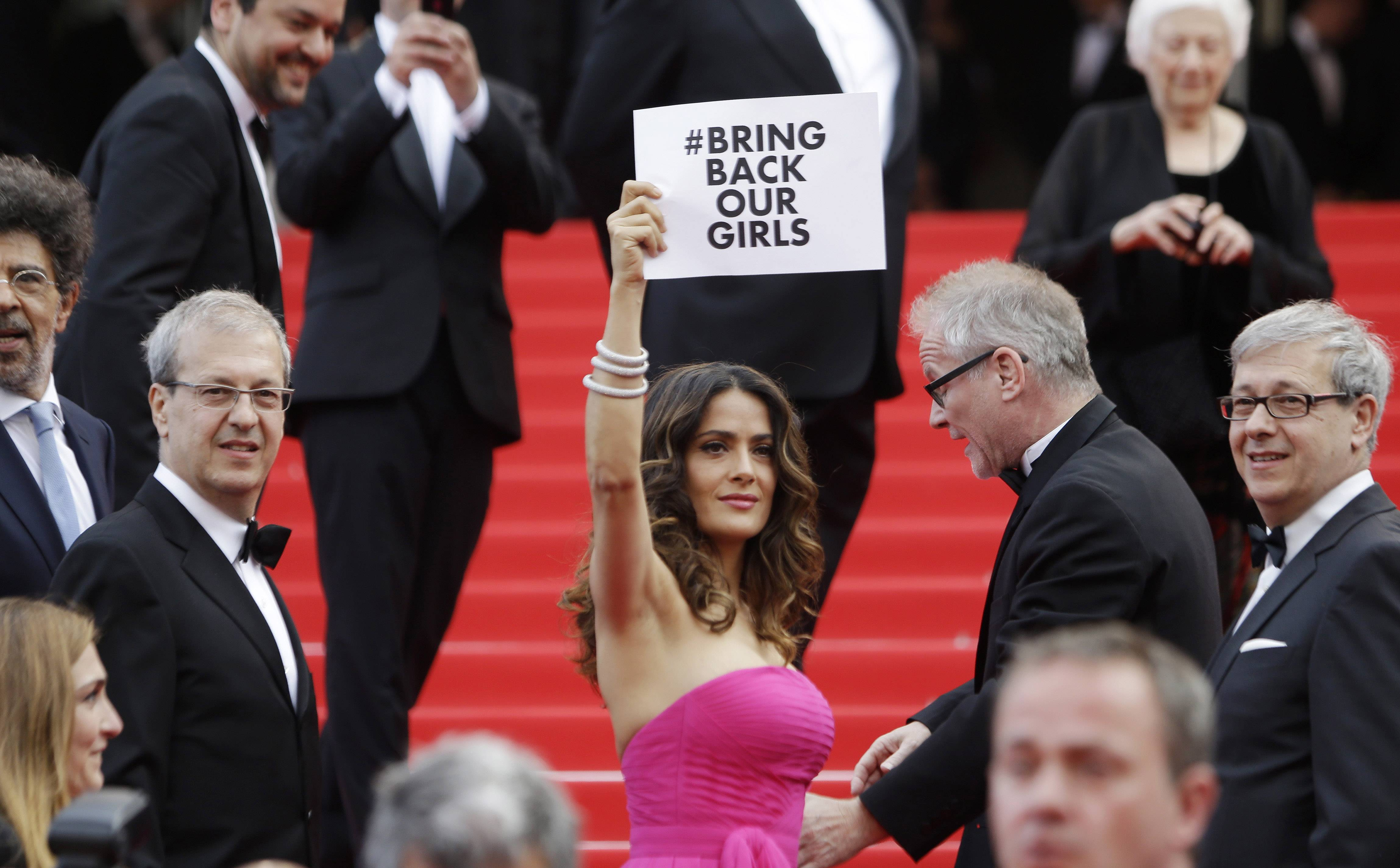 "Actress Salma Hayek holds up a sign reading ""bring back our girls,"" part of a campaign calling for the release of nearly 300 abducted Nigerian schoolgirls as she arrives for the screening of Saint-Laurent at the 67th international film festival, Cannes, southern France."