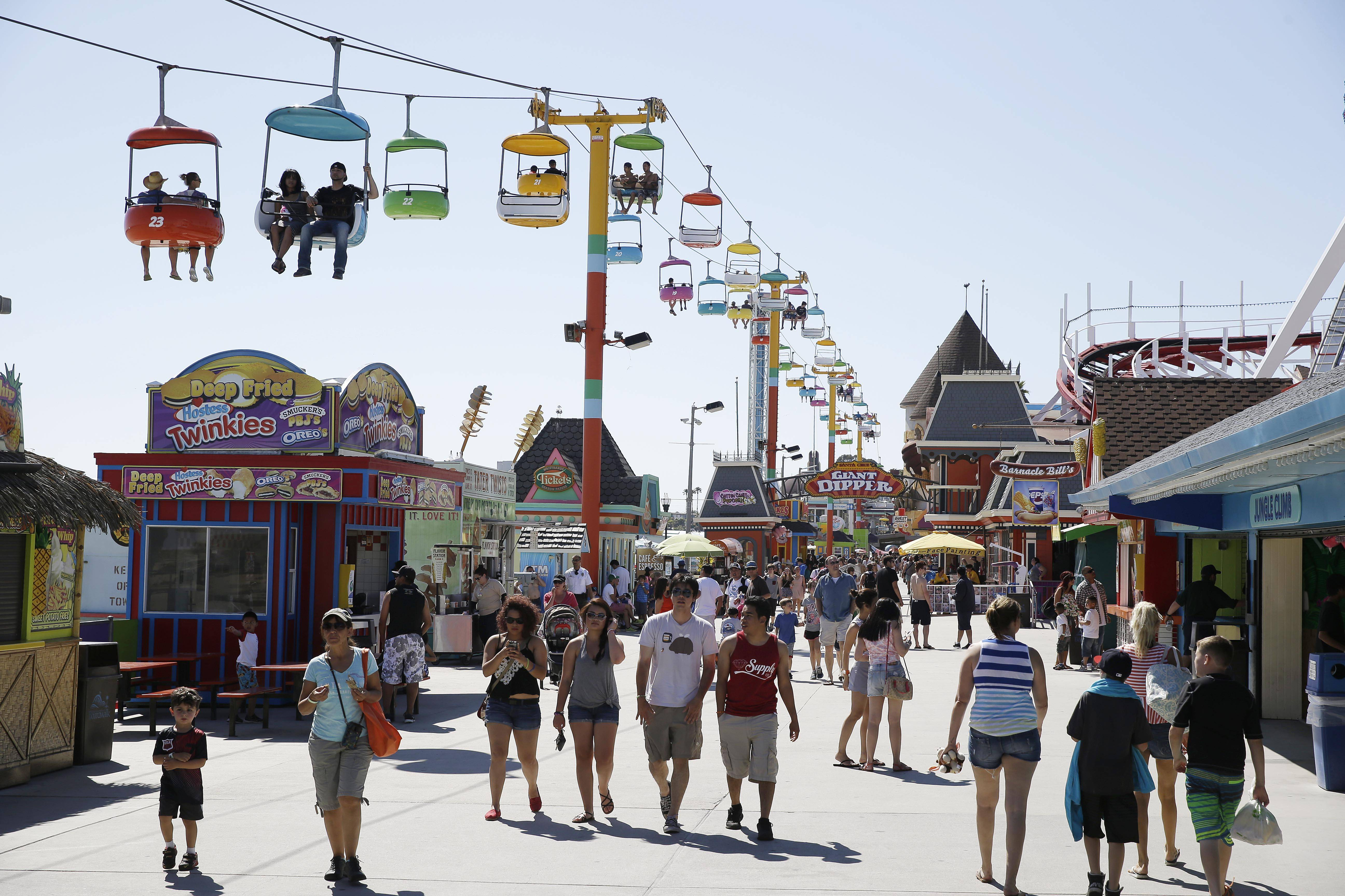 People walk below the Sky Glider and make their way along the Santa Cruz Beach Boardwalk in Santa Cruz, Calif. Riding the rides costs money, but there's no fee to stroll along the historic boardwalk and enjoy the sights and sounds.