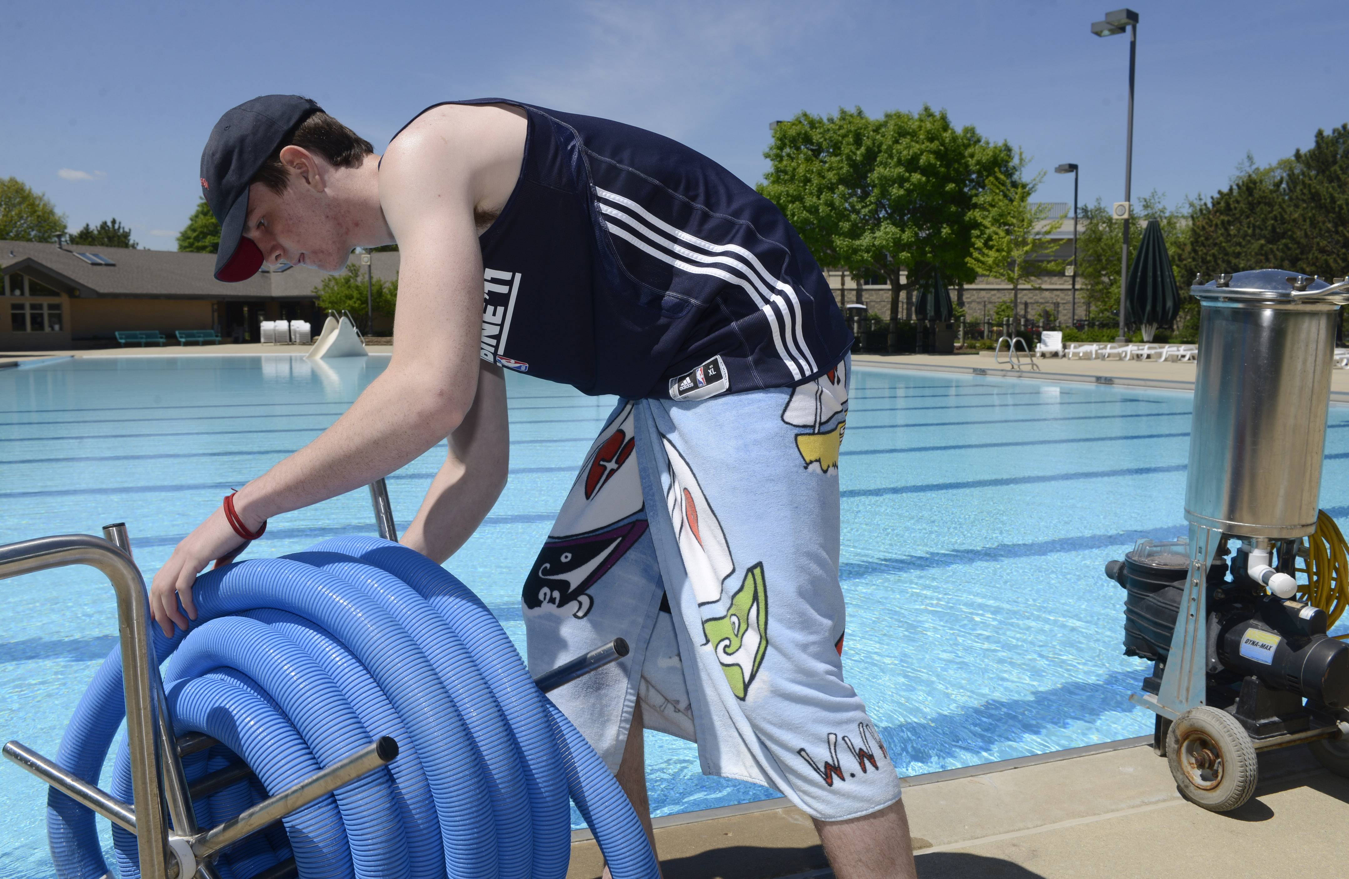 Lifeguard Tom Martin puts away cleaning equipment at Pioneer Park Pool in Arlington Heights, which is opening Saturday.