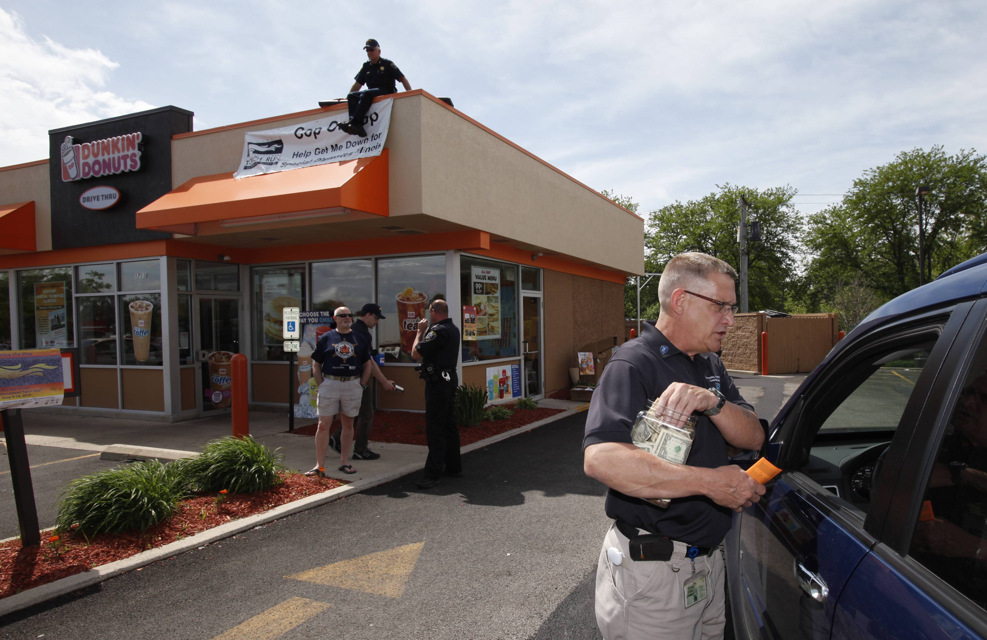 "St. Charles police community restitution coordinator Dan Orland talks with a drive-thru customer at the Dunkin' Donuts location during the 2013 ""Cop on a Rooftop."" This year's event will be Friday, May 30."