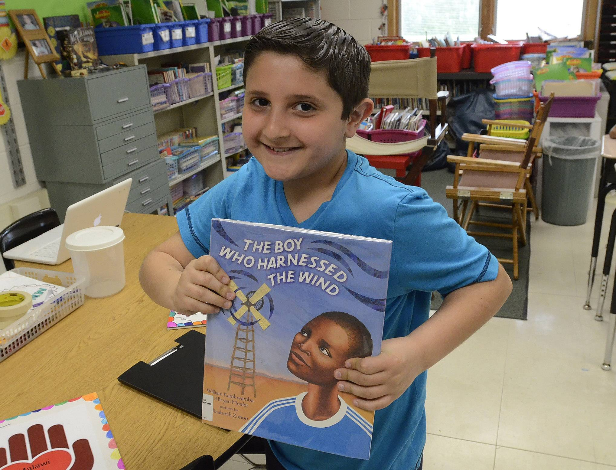 Angelo Bravos holds the book that inspired fourth-graders at Forest View School in Mount Prospect to raise money for the Malawi Heart Fund, which will provide hygiene kits for orphans at the Malawi Children's Mission.