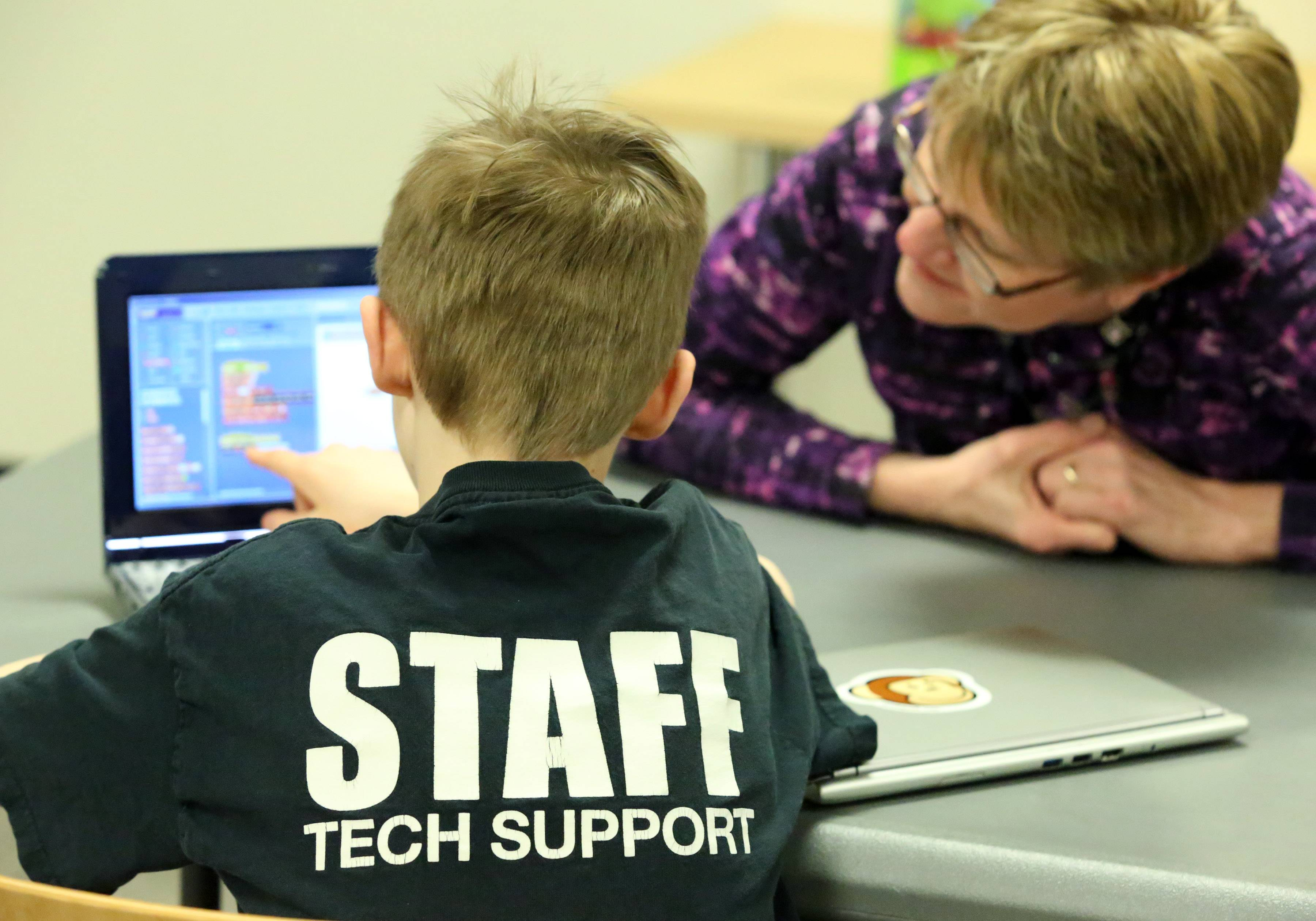 "Andy Merrill, 13, of Libertyville, explains a programing language he is using on his laptop to Ellen Jennings, teen librarian at Cook Park Library, during a teen program called ""Teen Tinkers and Minecraft"" in Libertyville."