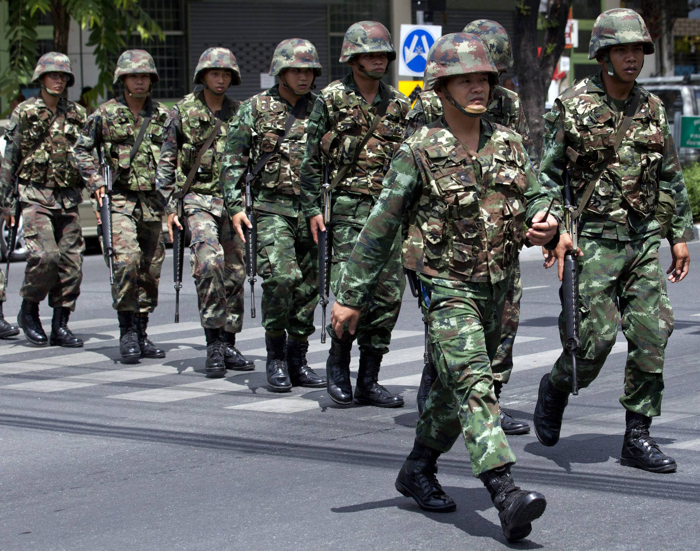 Thai soldiers patrol near the Army Club before former Prime Minister Yingluck Shinawatra arrives to report to Thailand's ruling military in Bangkok, Thailand, Friday, May 23, 2014.
