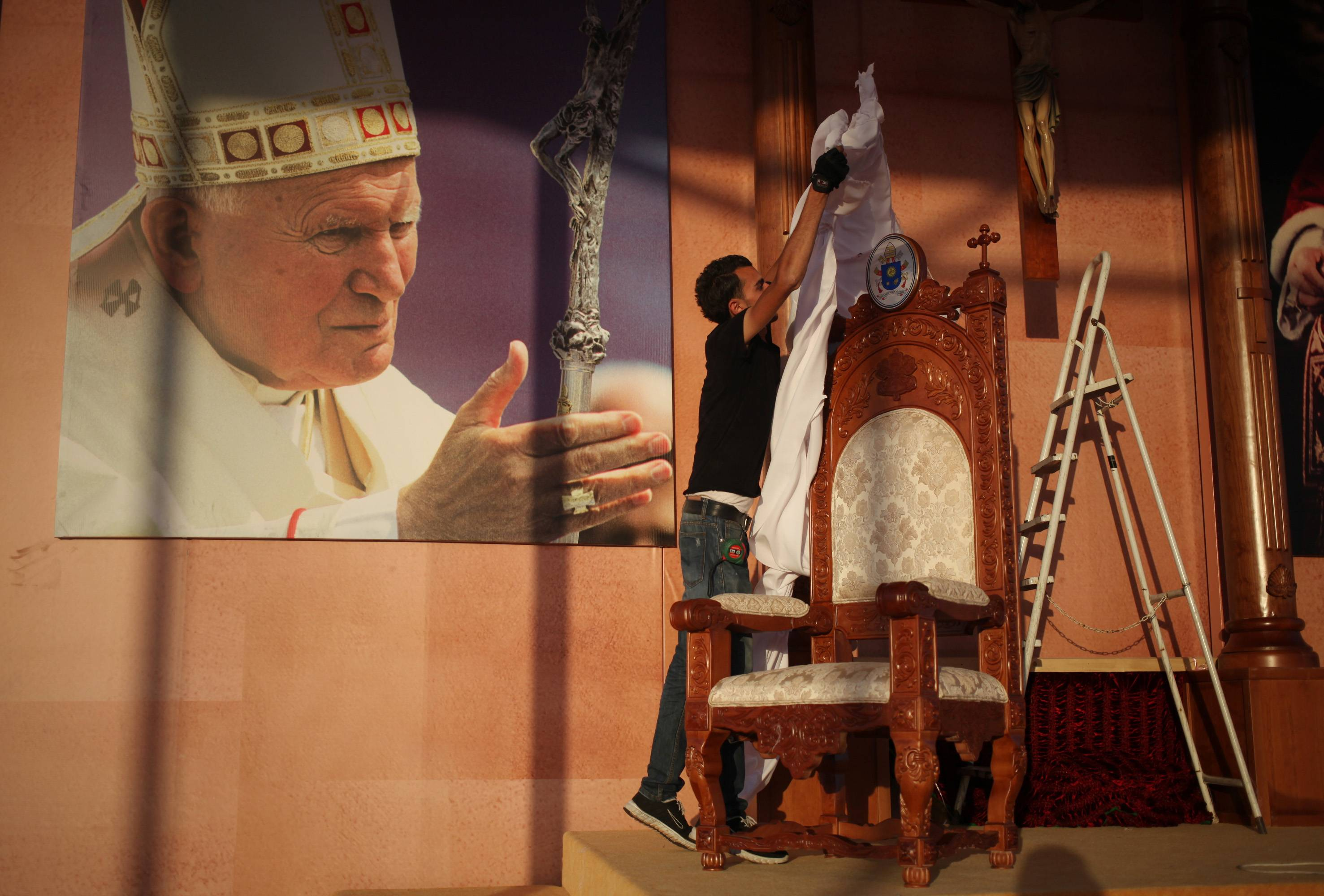 A Jordanian worker covers the chair that will be used by Pope Francis during a mass on Saturday at Amman's International Stadium in Jordan, Thursday, May 22, 2014. The Photo on the wall is of the late Pope John Paul II.
