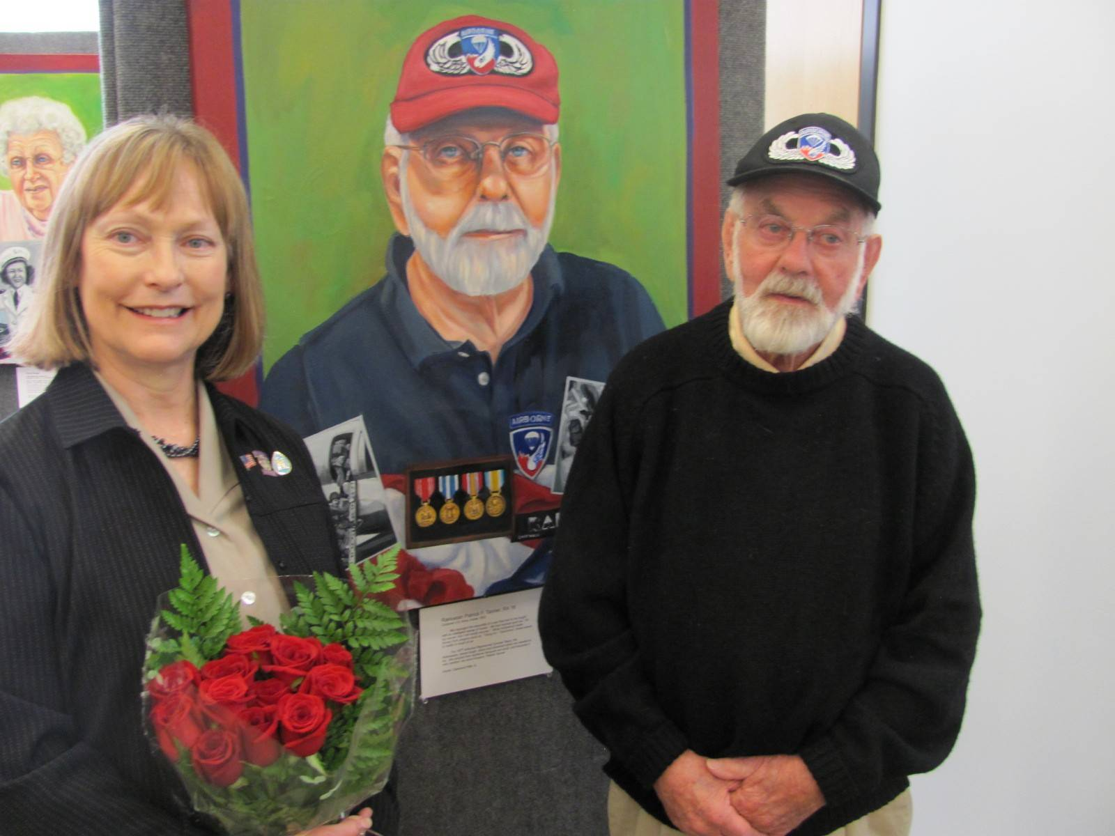 Algonquin artist Jeanine Hill-Soldner with the subject of one of her portraits of area veterans, Cpl. Patrick Tanner, during a reception at the Addison Public Library.