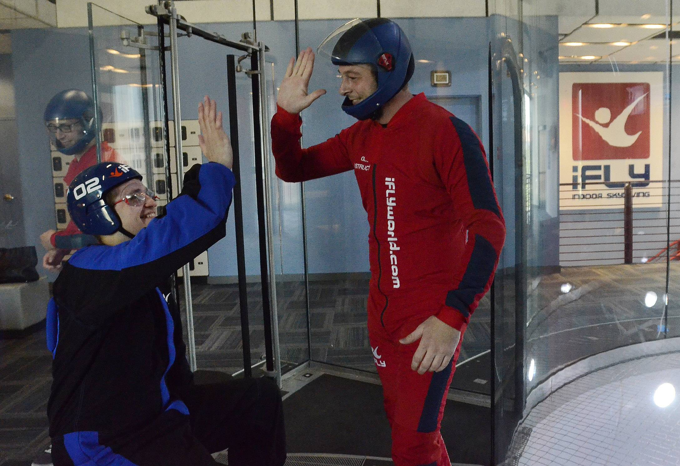 Daily Herald reporter Chris Placek is congratulated by instructor Gabriel Roth after taking an indoor sky diving flight at iFLY in Rosemont.
