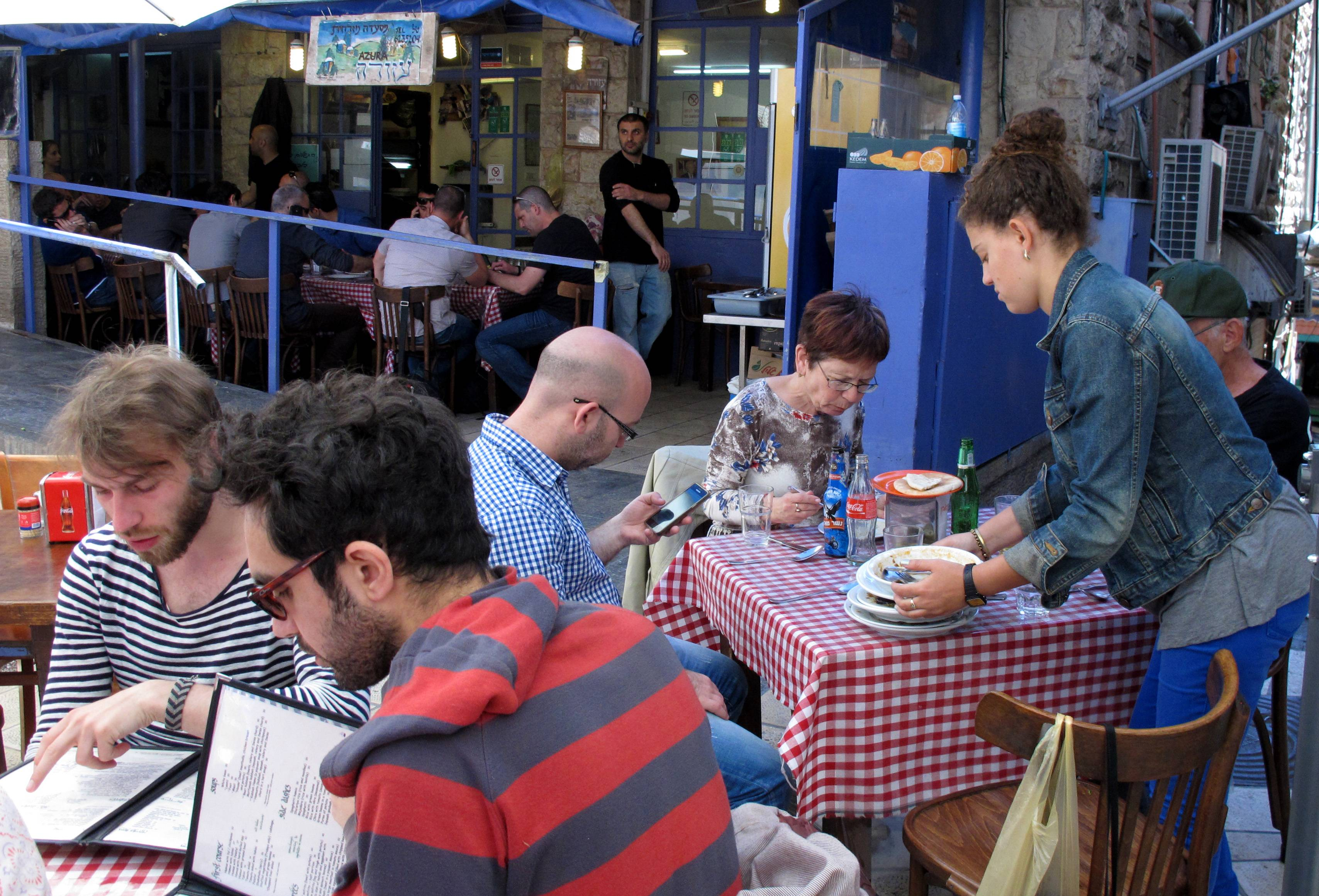 Diners enjoy a meal at the Azura restaurant in Jerusalem's Mahane Yehuda market. The family-run institution is famous for its Turkish-inspired delicacies that are slow-cooked to perfection atop kerosene burners.