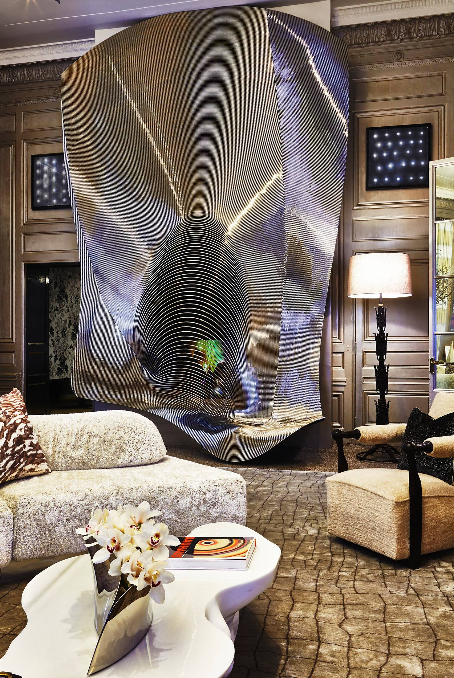 "Room 2 of the Kips Bay Show House 2014 in New York is ""A Study in Contrast,"" designed by Tony Ingrao and Randy Kemper. The sofa floats in the center of the room like a sculpture, and the fire screen by Ron Arad was originally built for an Aspen ski lodge."