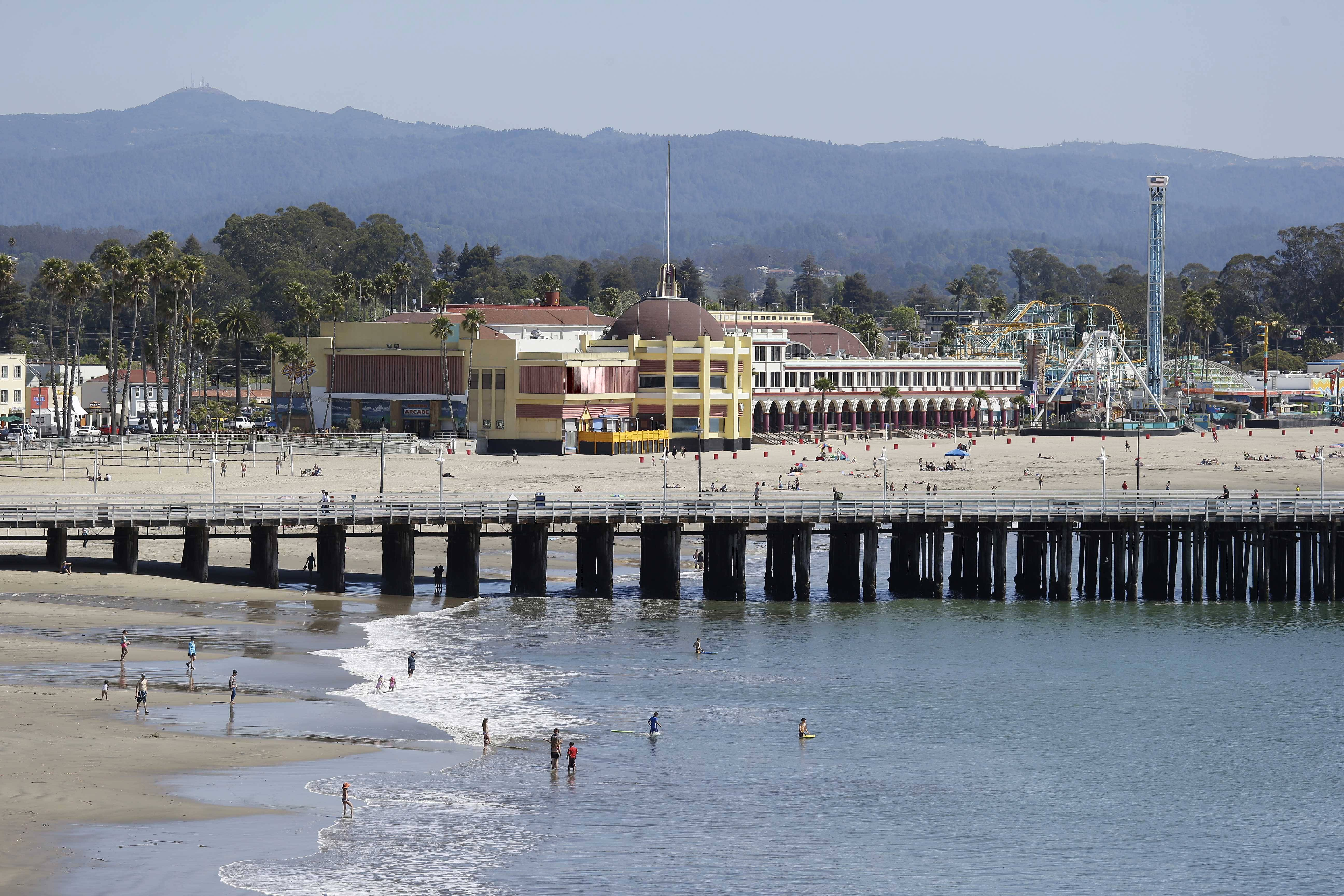People enjoy the beach with the hundred-year-old wharf and Santa Cruz Beach Boardwalk in the background in Santa Cruz, Calif. Walking the beach, boardwalk and wharf are all free things one can enjoy when visiting Santa Cruz.