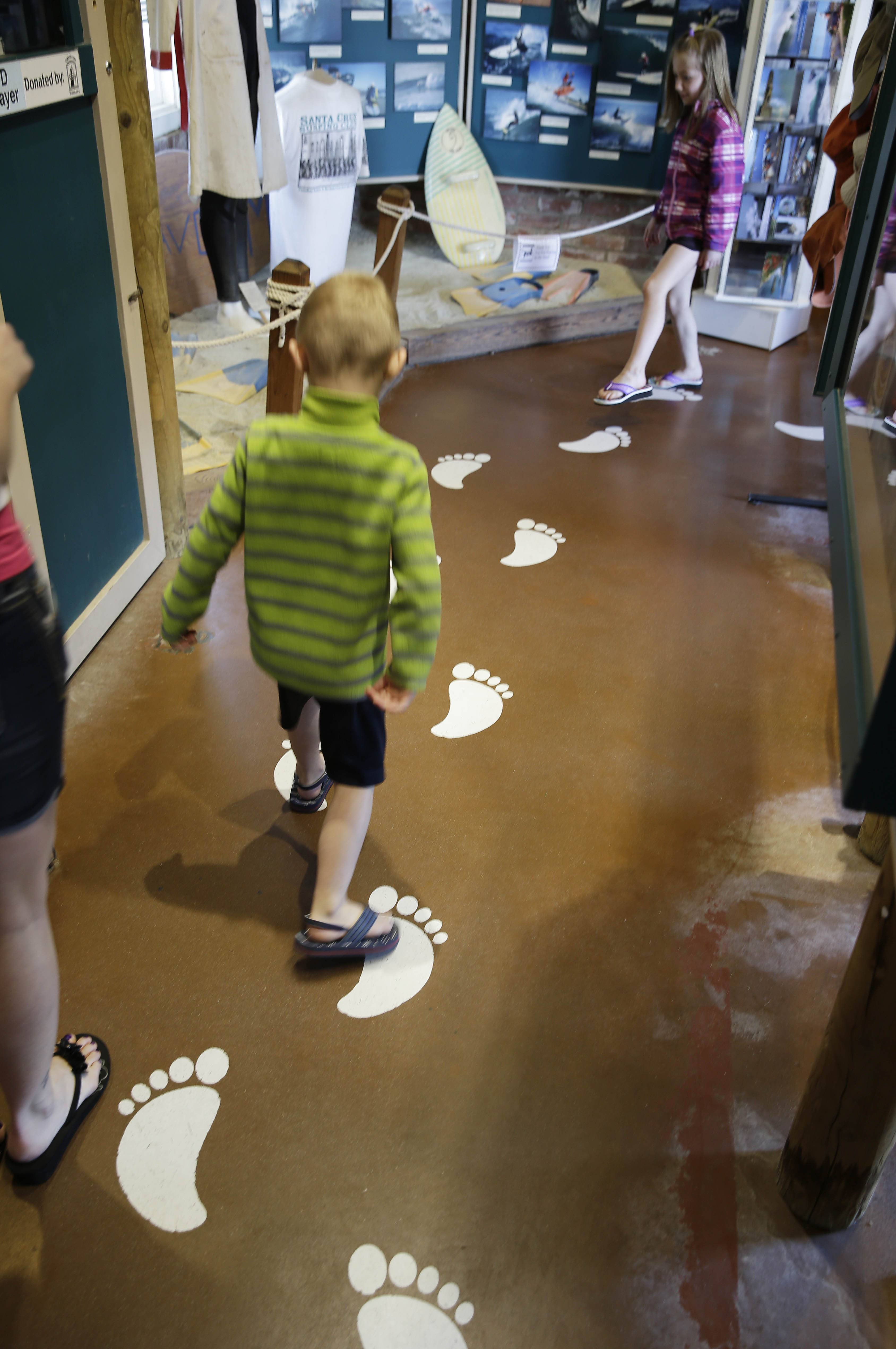 Children follow along painted footprints inside the Santa Cruz Surfing Museum in Santa Cruz, Calif.