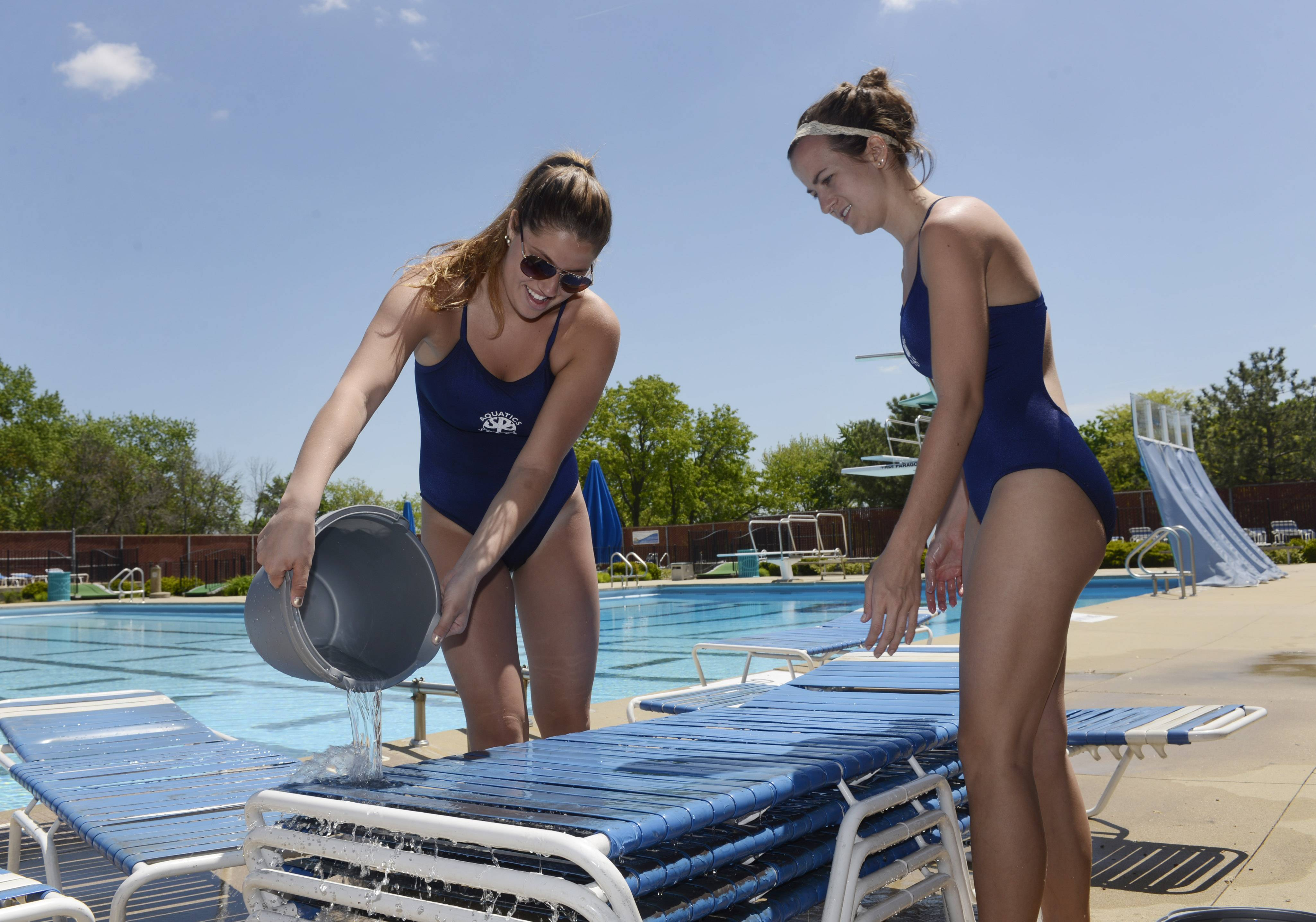 Lifeguard Ema Cigerova, left, and pool manager Laura Torpe clean chairs Friday in preparation for Saturday's opening of the Bock Neighborhood Center and Park pool in Schaumburg.