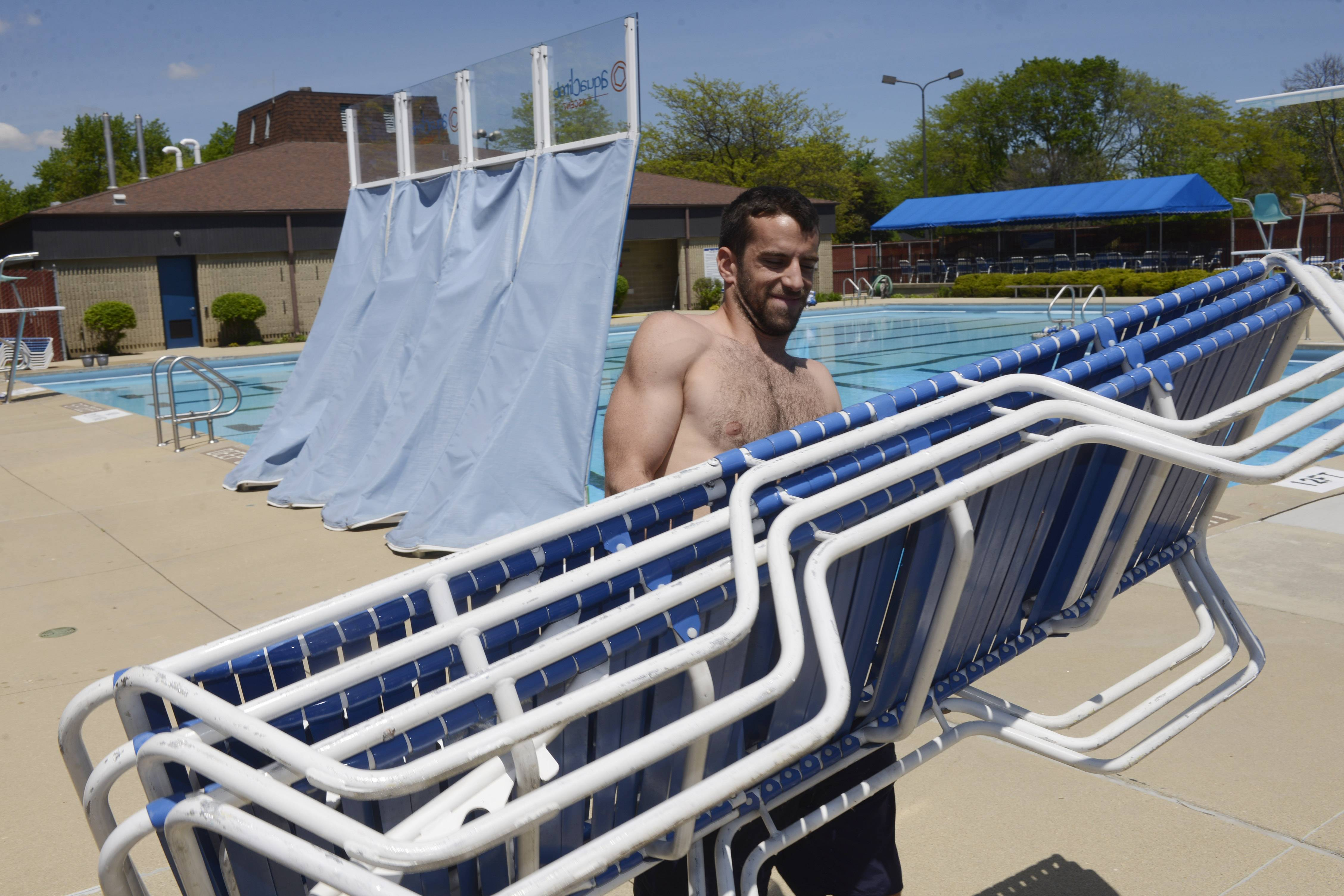 Lifeguard Daniel Serna-Geitz carries chairs to set up around the pool at the Schaumburg Park District's Bock Neighborhood Center and Park.