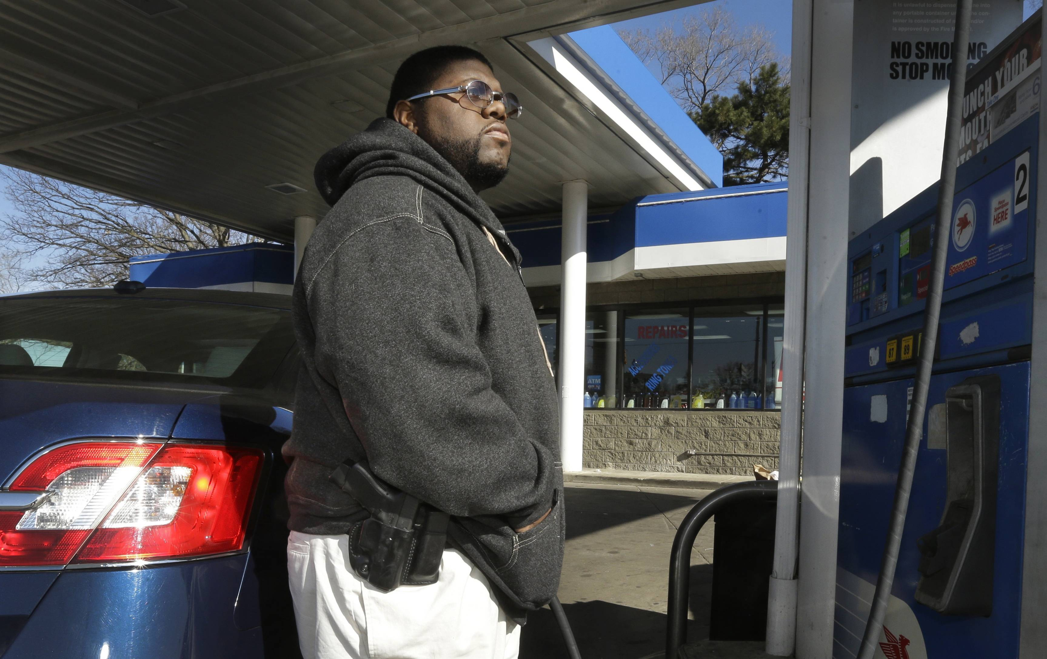 To avoid becoming a carjacking victim, security guard Greg Champion wears a handgun on his hip whenever he's pumping gas in Detroit.