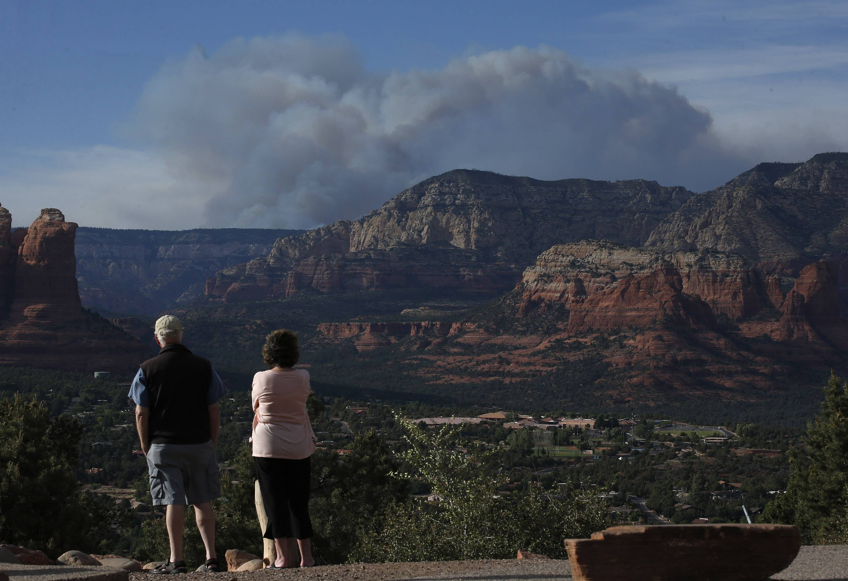 Tourists watch the Slide Fire from a scenic overlook as it burns up Oak Creek Canyon nearby on Thursday, May 22, 2014, in Sedona, Ariz. The fire has burned approximately 4,800 acres and is zero percent contained.