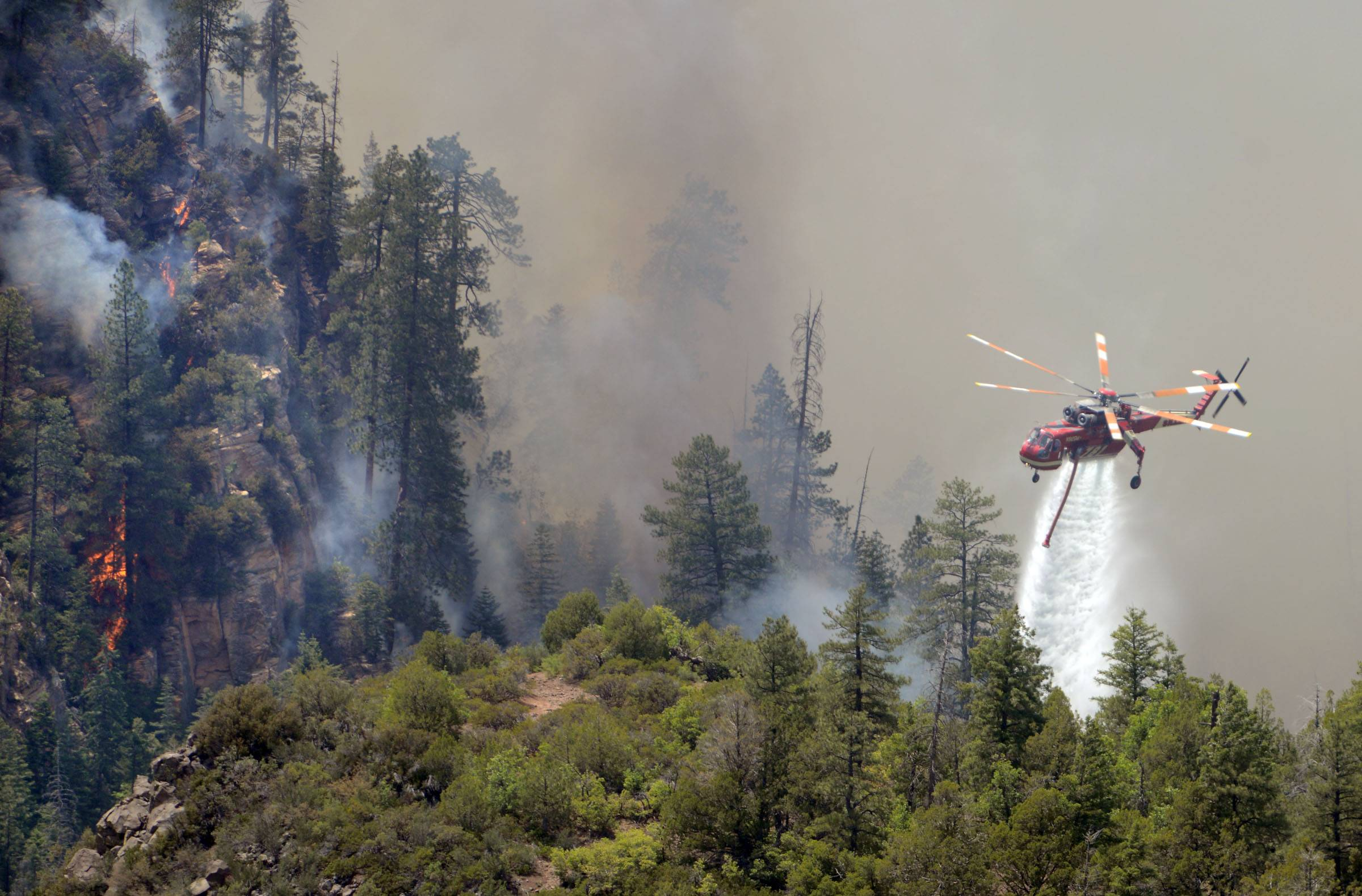 A firefighting helicopter drops water on a forest fire in Oak Creak Canyon in Sedona, Ariz., on Thursday May 22, 2014. The human-caused Slide Fire started Tuesday and has burned more than 11 1/2 square miles in and around Oak Creek Canyon, a scenic recreation area along a highway between Sedona and Flagstaff that normally would be teeming with tourists as the Memorial Day weekend approaches.