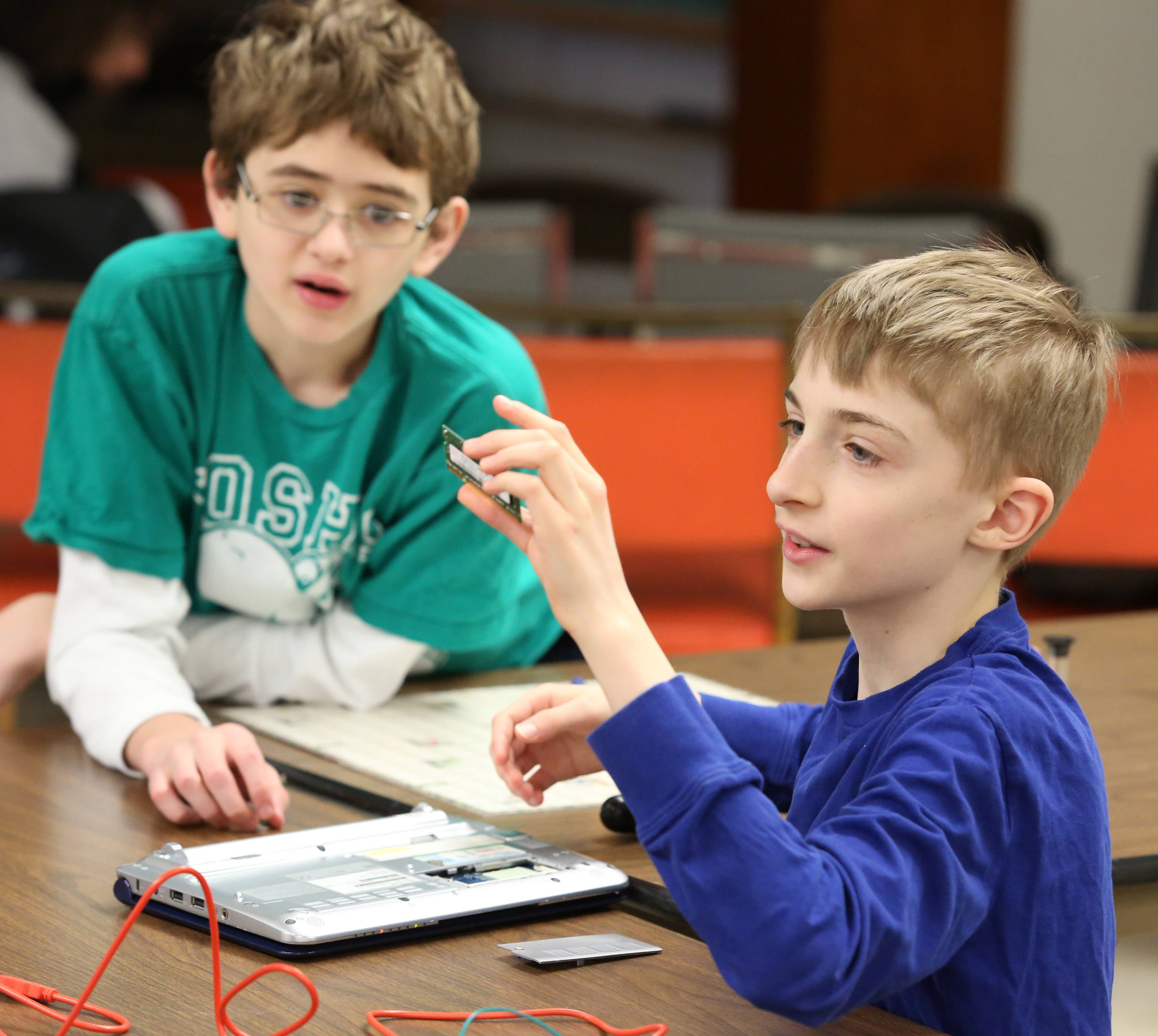 Sam Jaffe, 13, left, of Glenview, left, is surprised to see Andy Merrill remove a small electrical board from his laptop during a Curiosity Hacked Guild meeting at Central United Methodist Church in Skokie.